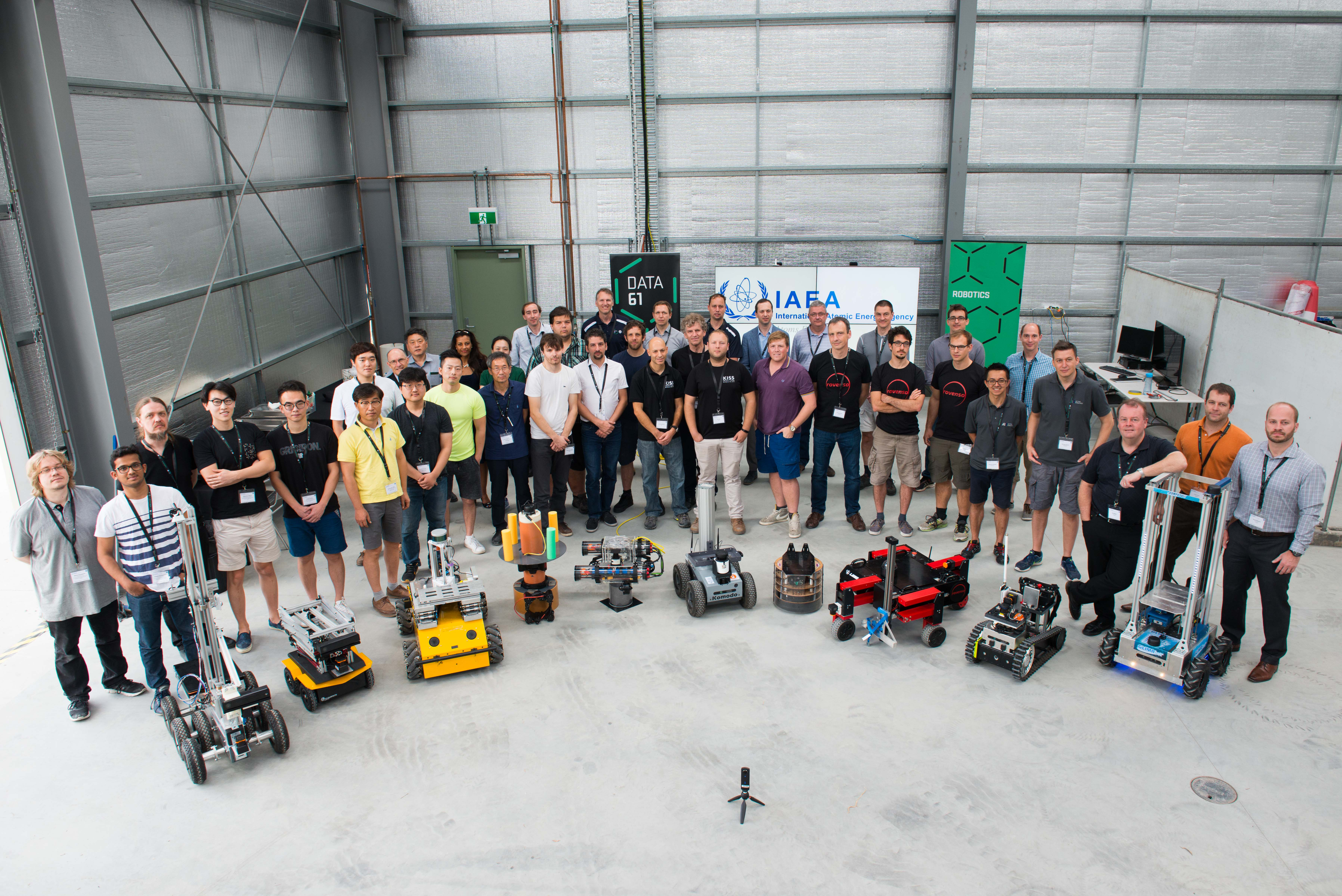 In a warehouse, a large group of people stand in a semi-circle with several small robots positioned in front of them.