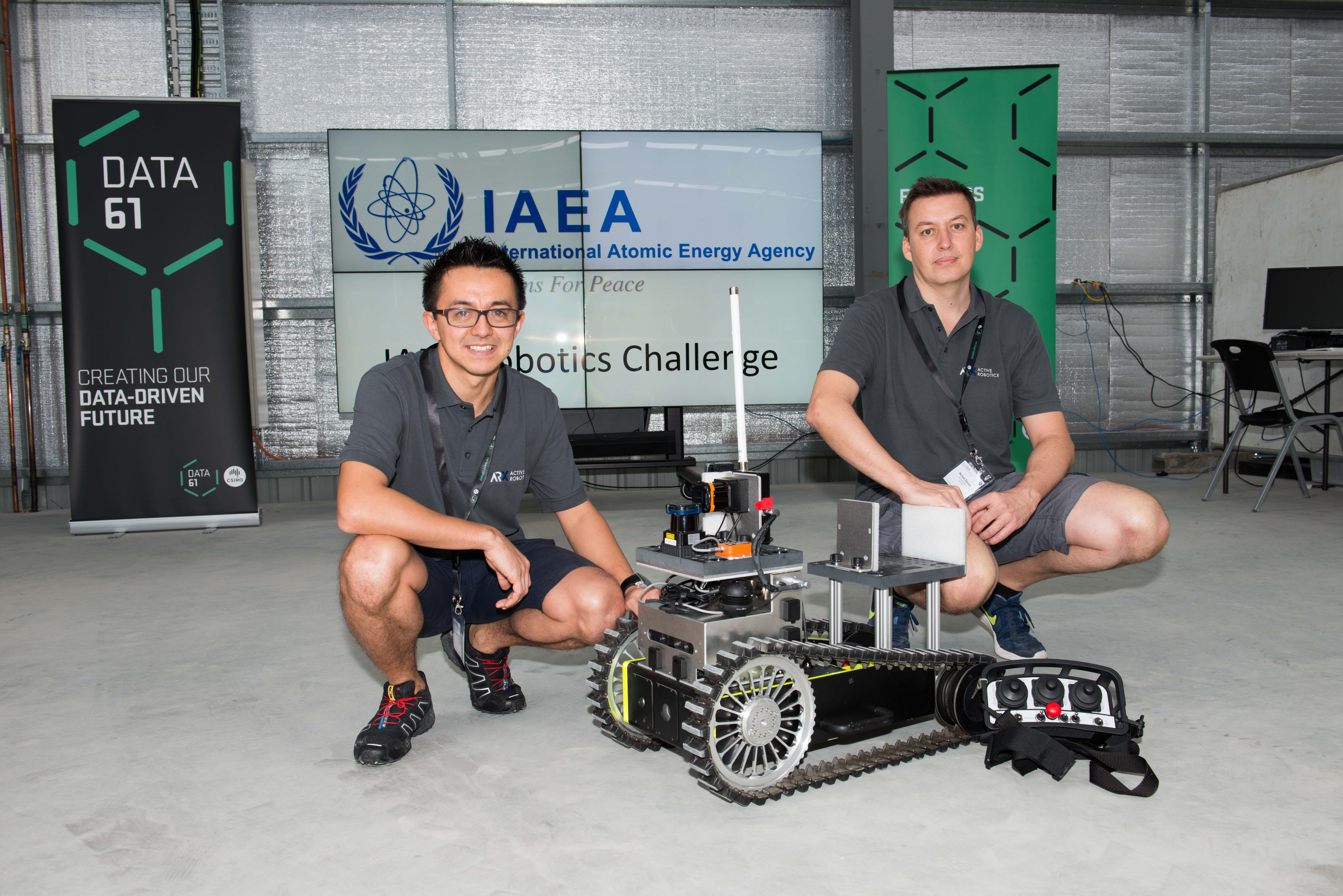 Two men kneel behind a caterpillar tracked robotic device.