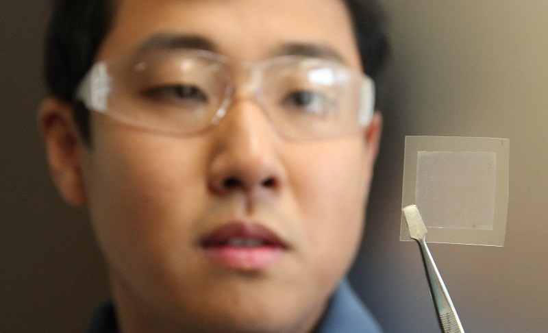 Man wearing safety glasses holding a piece of graphene with tweezers