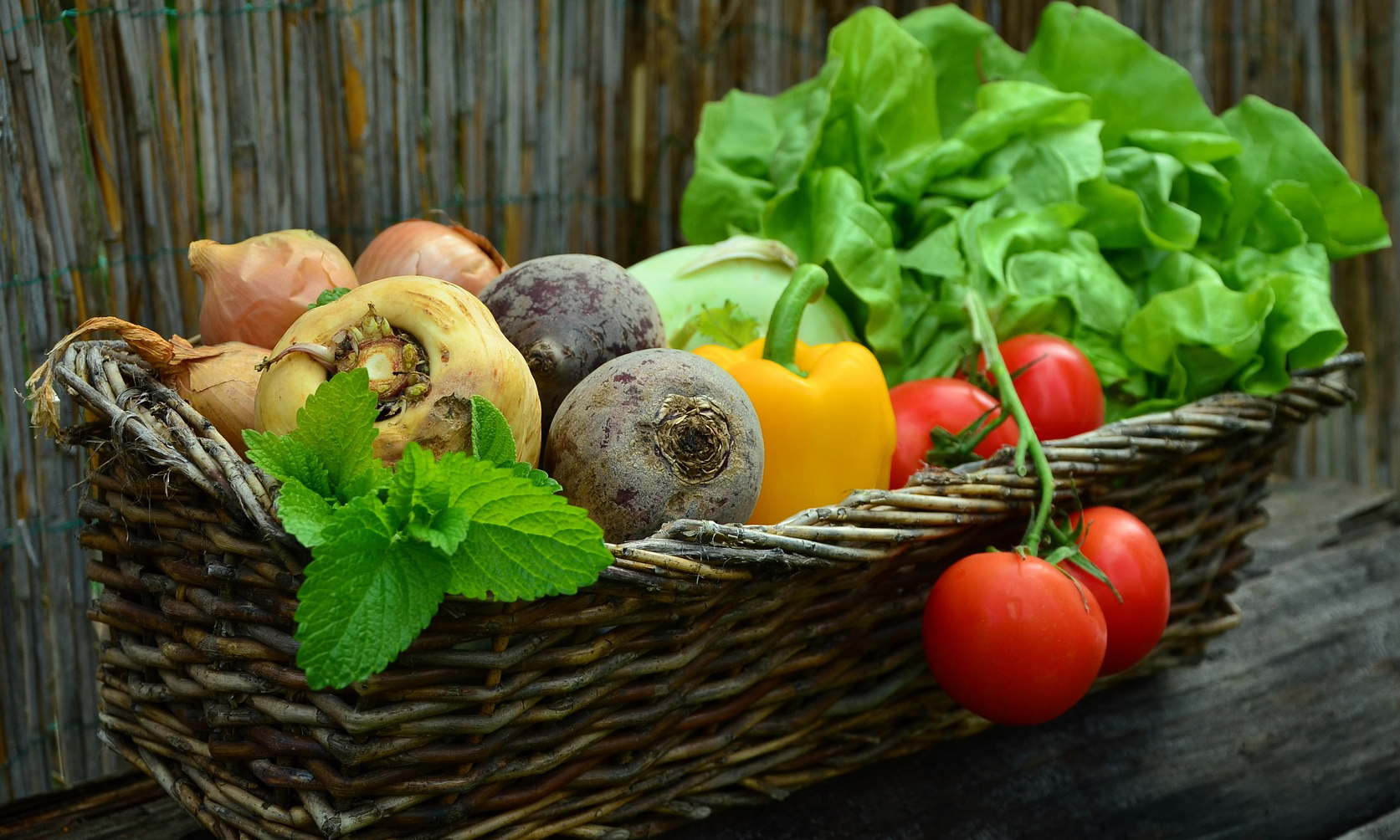 Assortment of fresh fruit and vegetables in a basket.