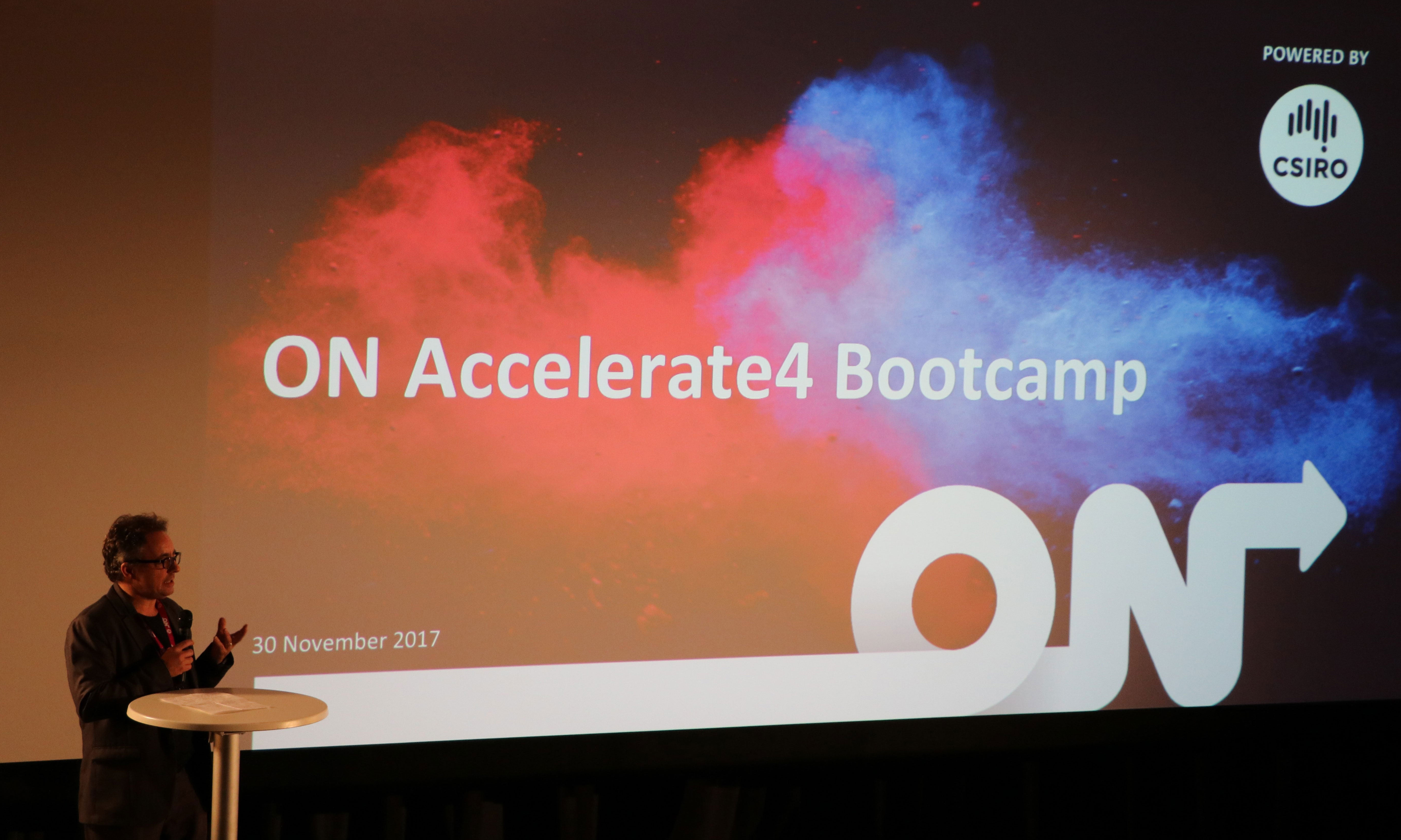 Person on stage giving a presentation with a backdrop image containing the words ON Accelerate4 Bootcamp, with the ON logo at the bottom and the Powered by CSIRO logo at the top.