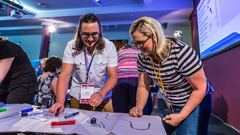 Two primary teacher participants standing at a desk containing STEM related equipment.