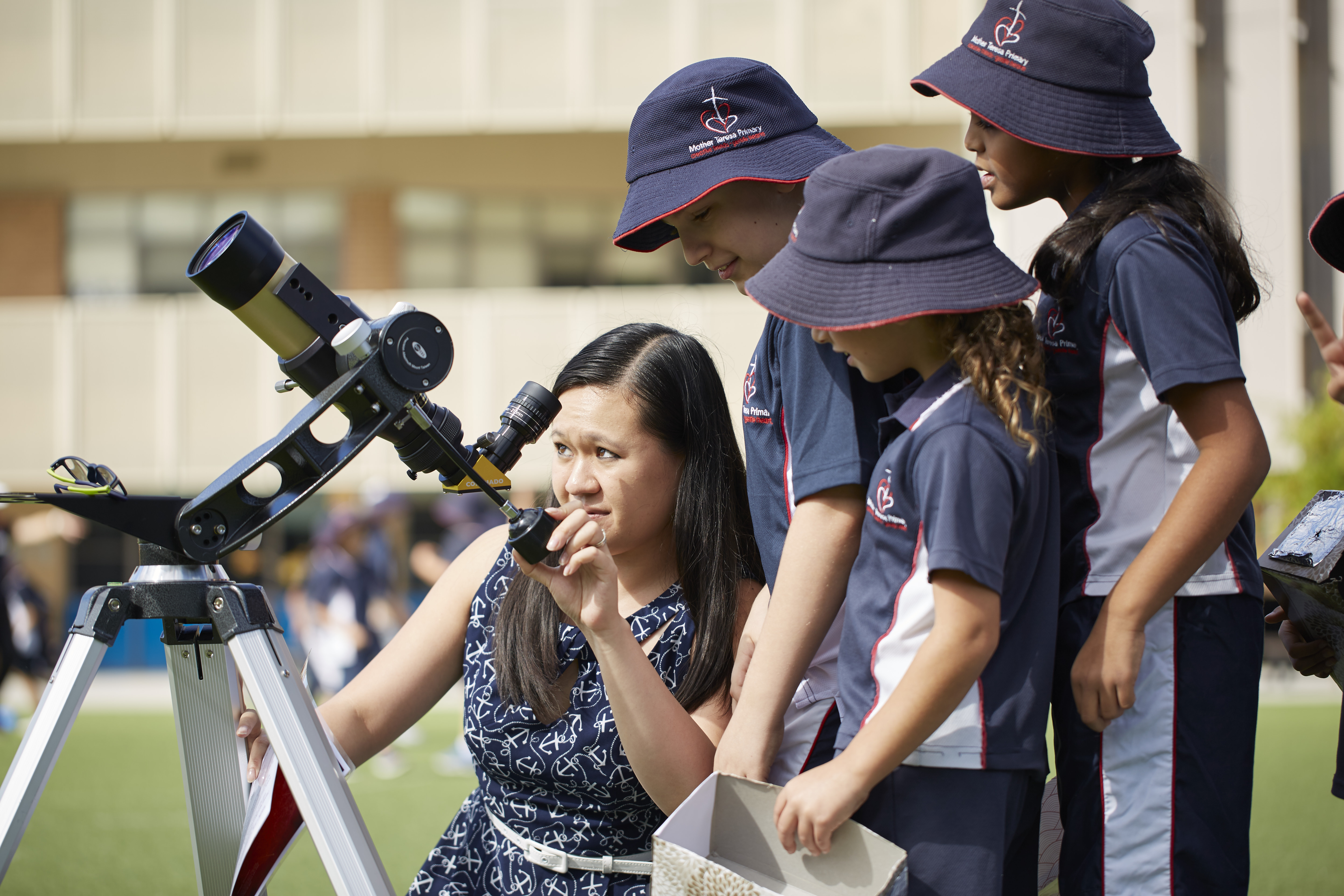 Scientist looking through a telescope with school children looking on.