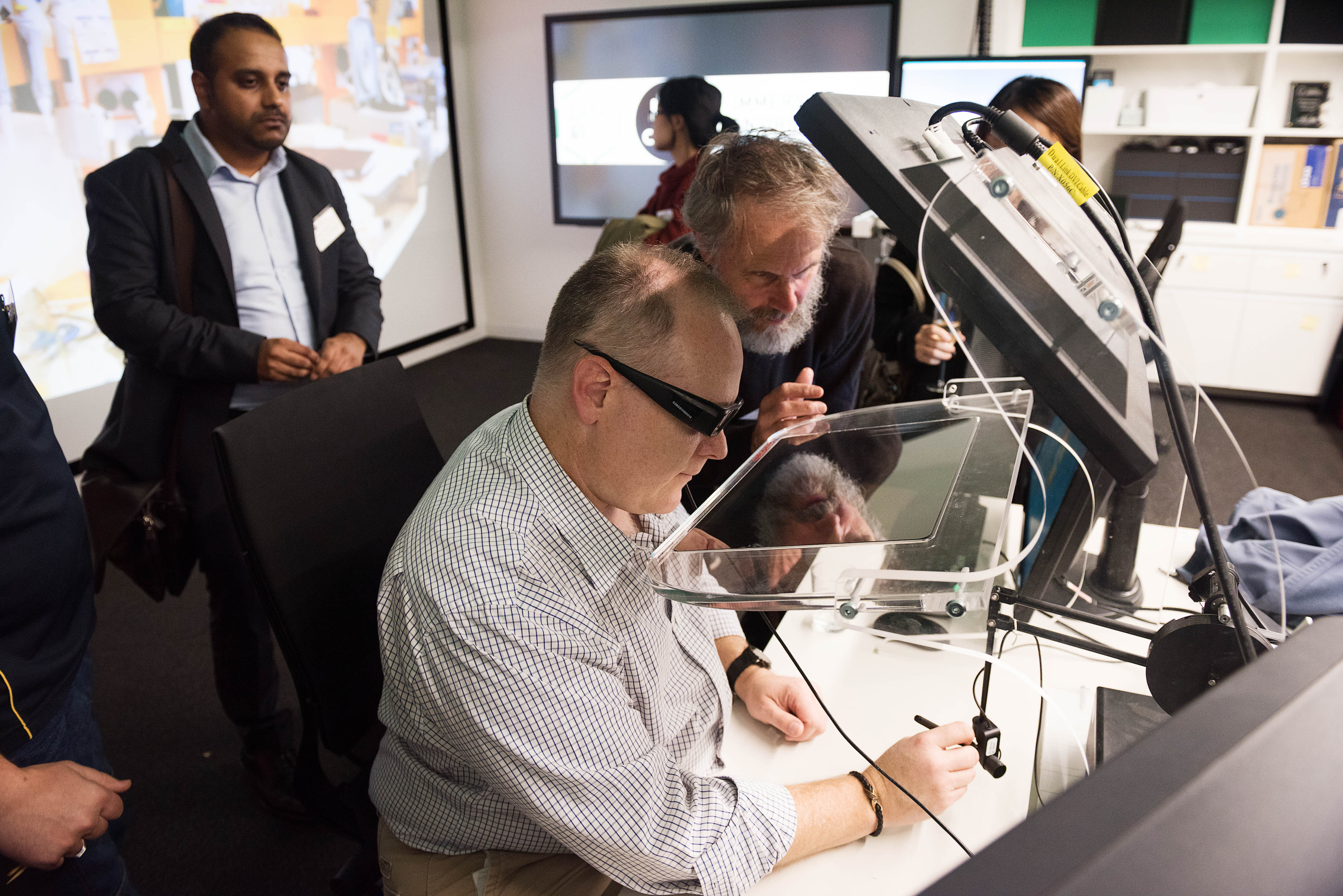 People sitting at a desk demonstrating AR and VR technology.