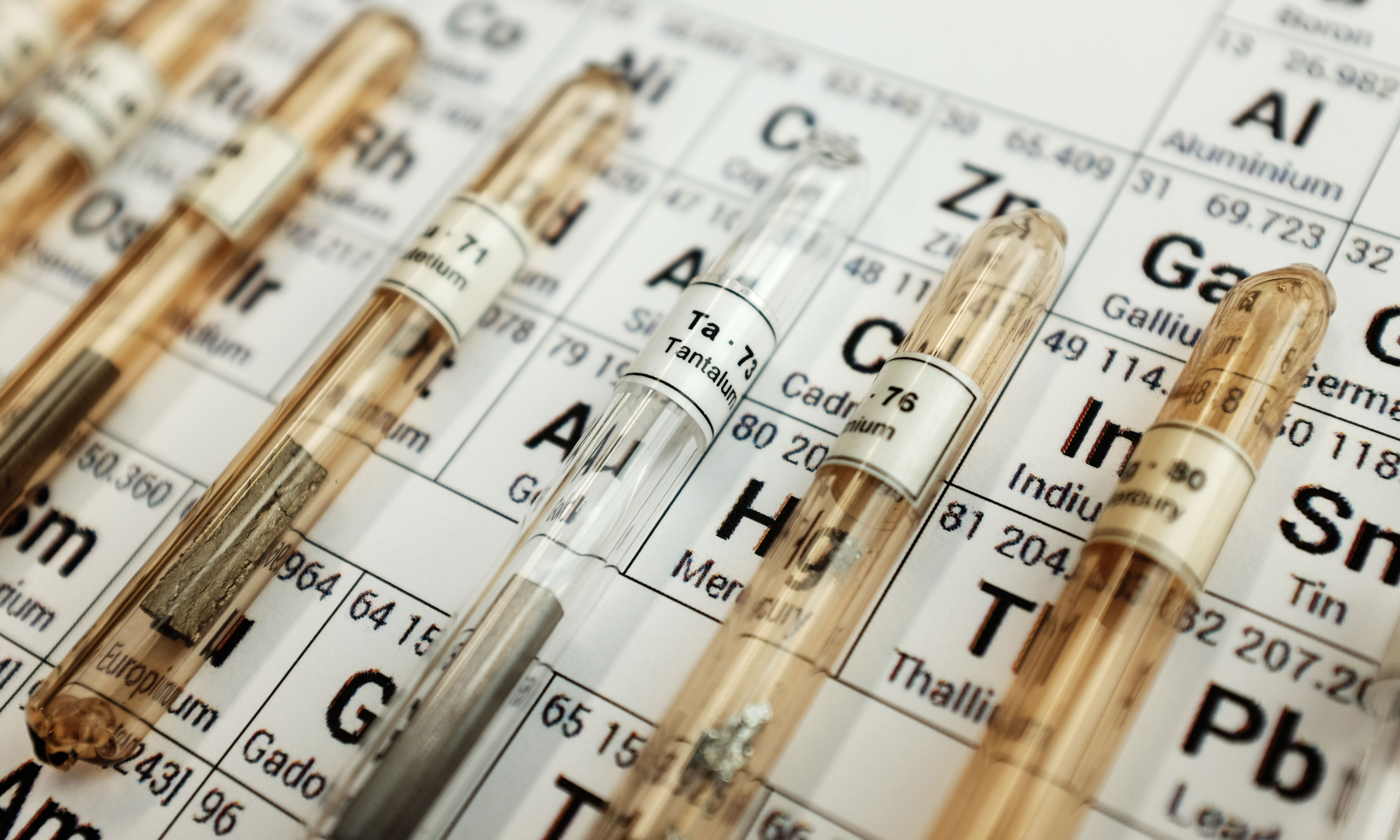 Photon assay tubes of x-ray gold analysis lined up across a copy of the periodic table.