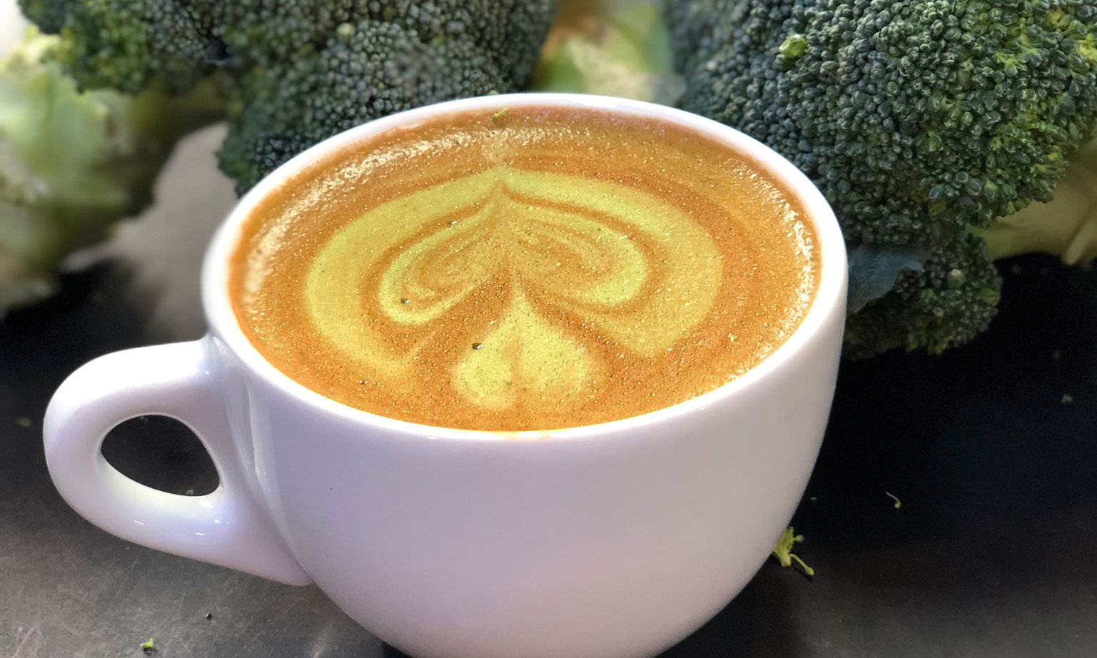 A broccoli latte on a table with broccoli florets in the background.