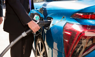 man in suit filling up hydrogen vehicle with fuel