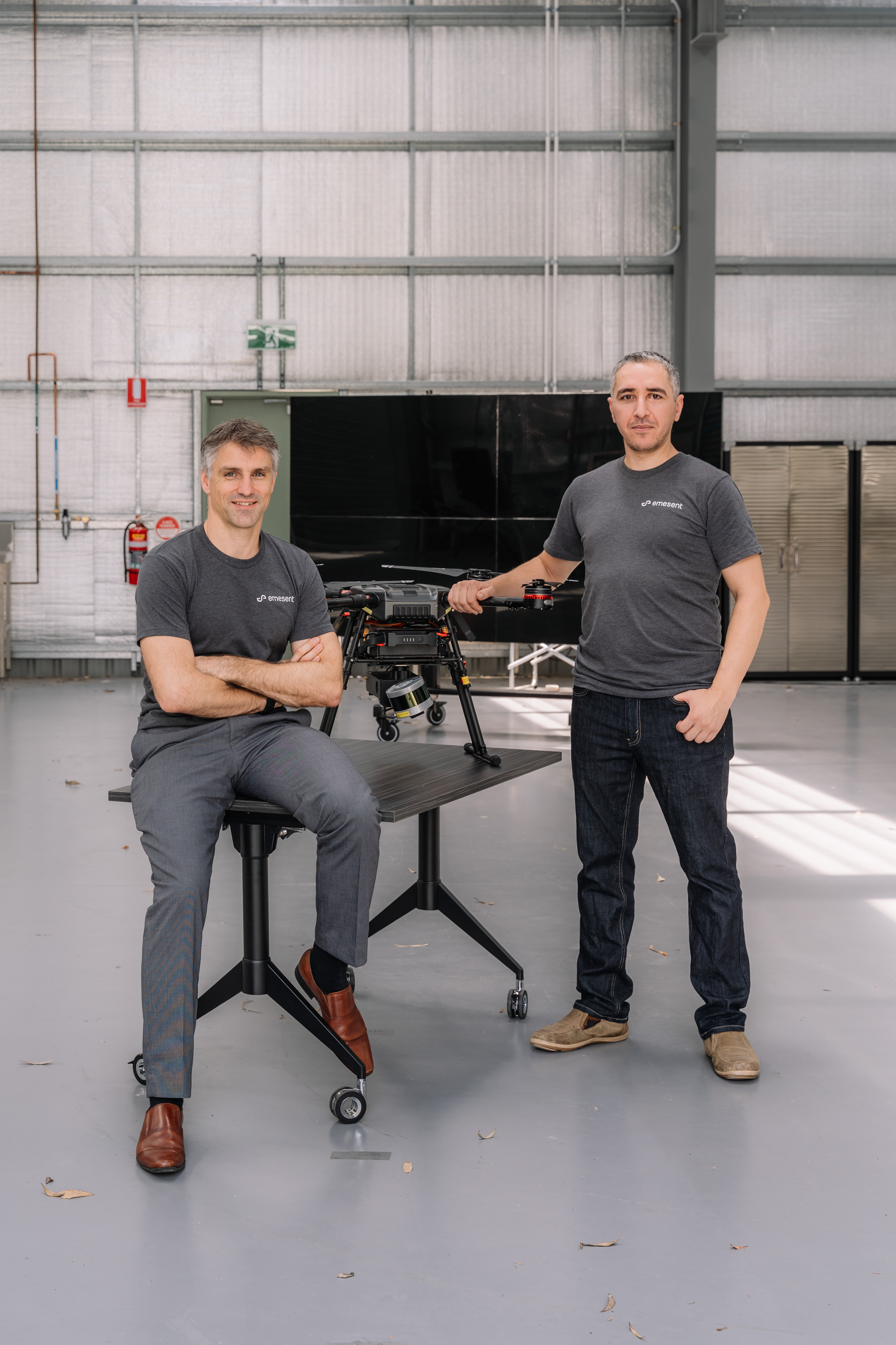Stefan Hrabar and Farid Kendoul standing next to a chair with a drone resting on it.