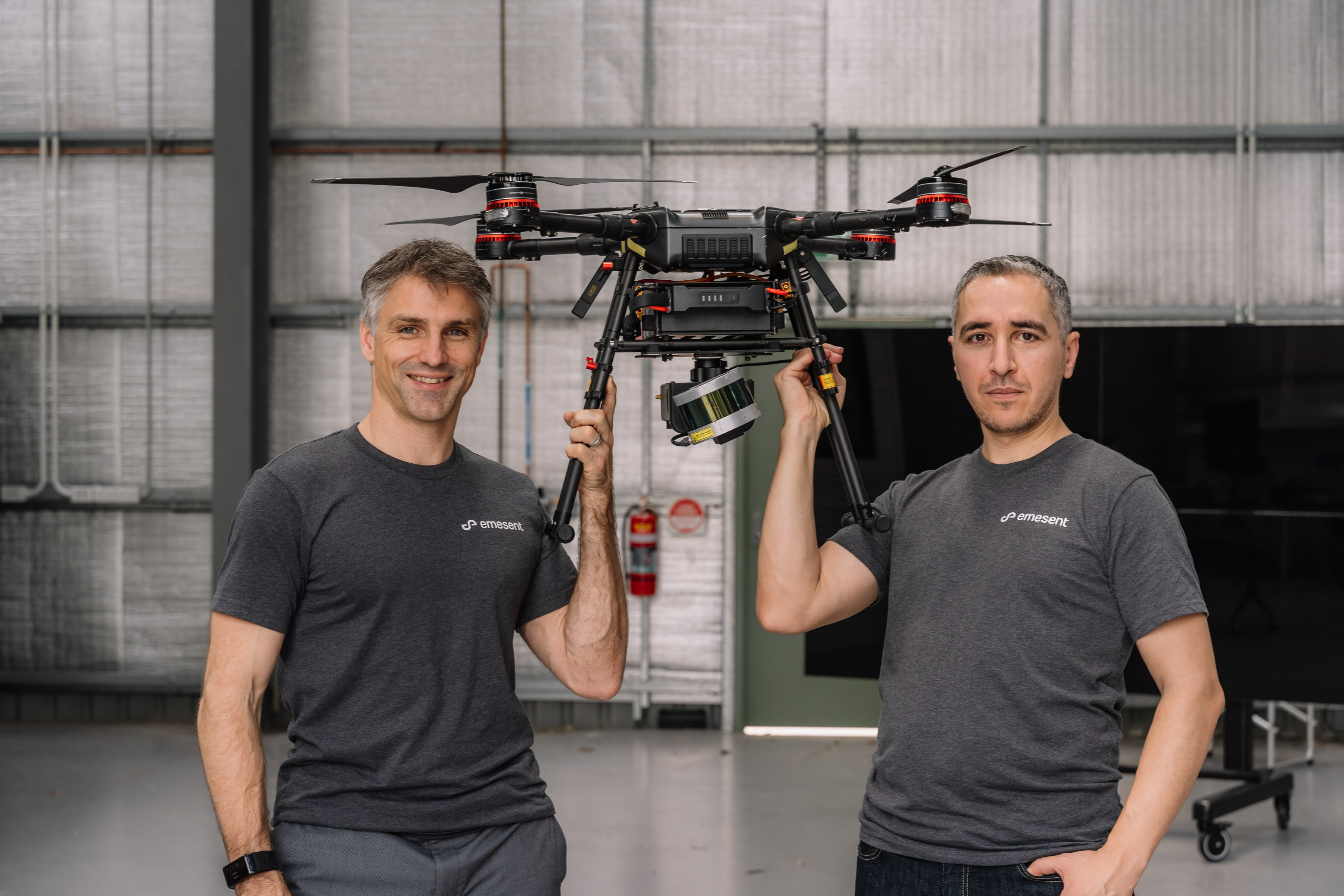 Emesent co-founders Stefan Hrabar and Farid Kendoul holding up a drone between them.