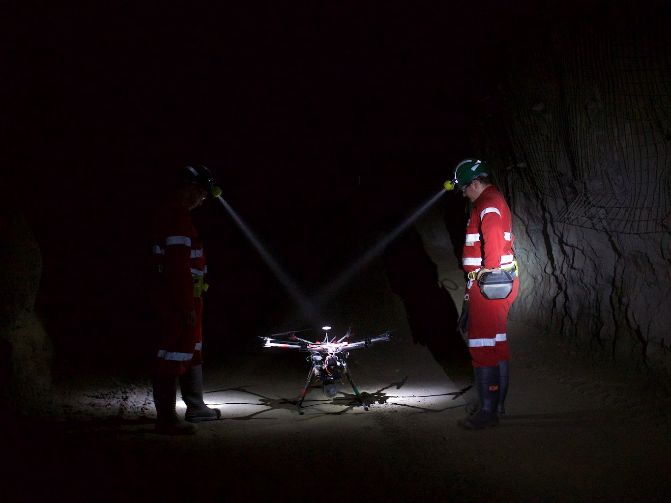 Emesents Hovermap in an underground mine flanked by two people in high-vis clothing wearing hard hats with head lamps.