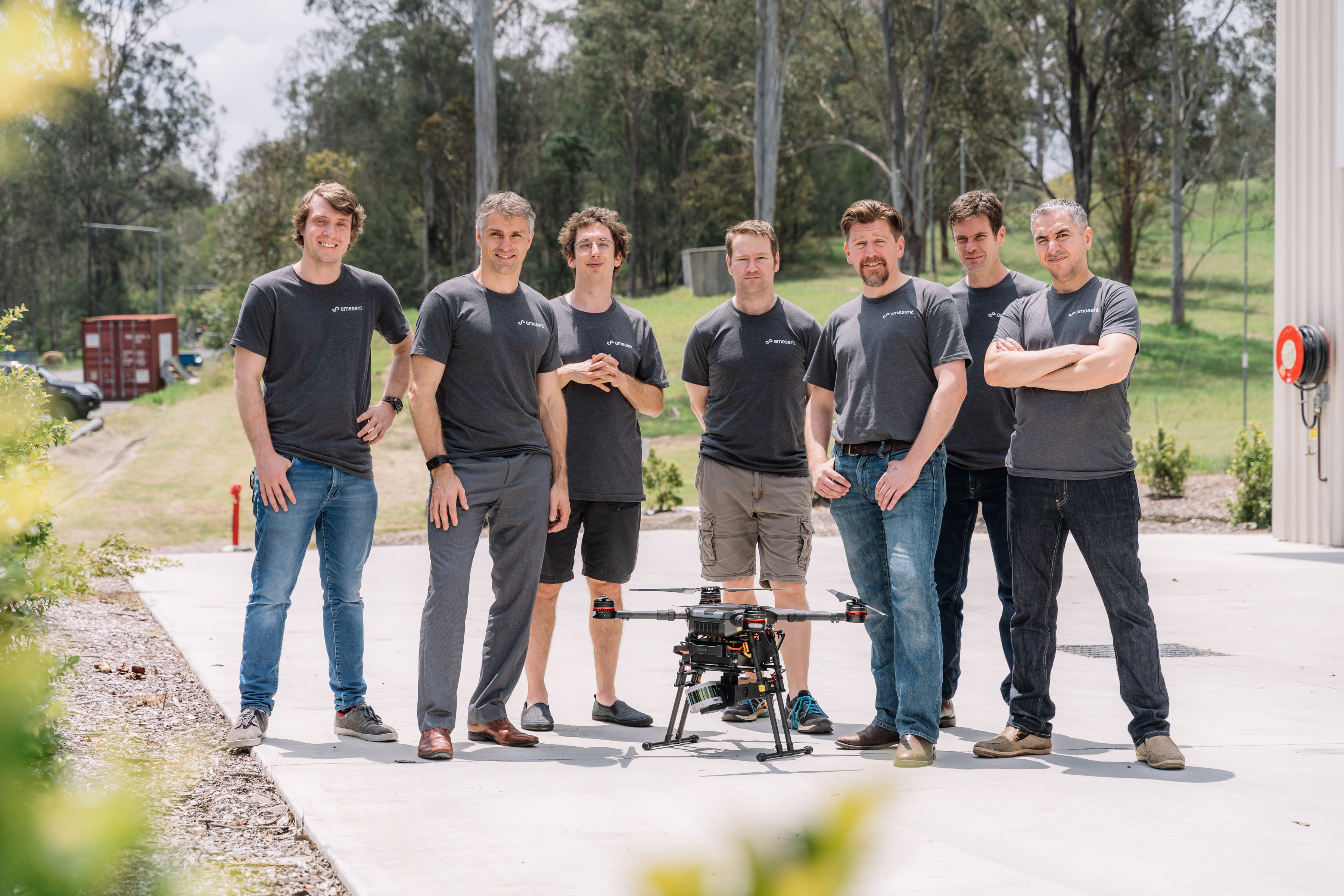 The Emesent team standing outside behind a drone on the ground.