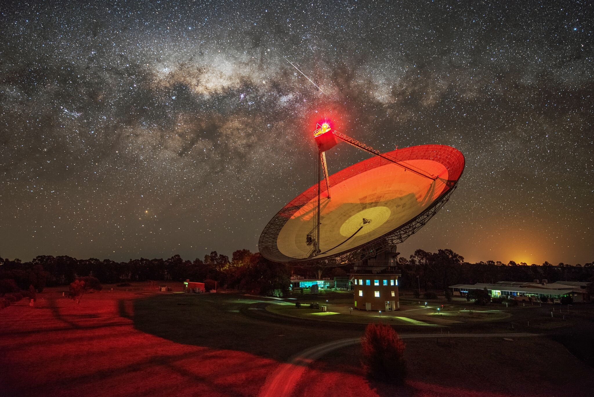 Radio telescope at night illuminated with red light under a starry sky.
