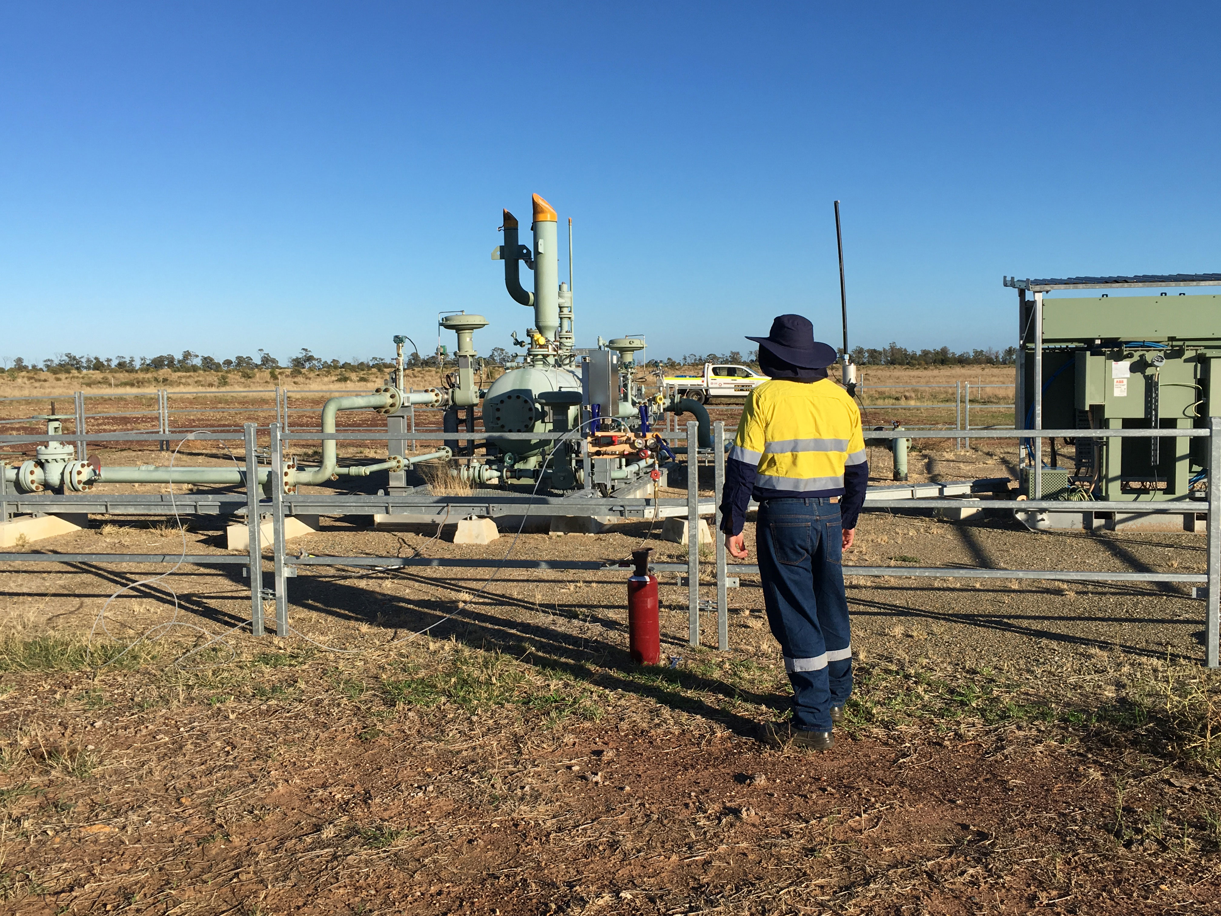 Person in workwear standing at a coal seam gas well.