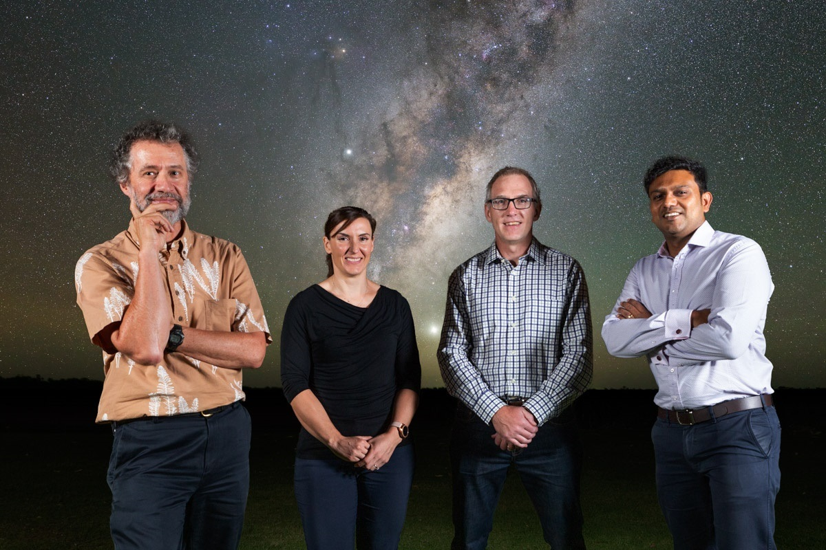 Antony Schinckel, Rebecca Wheadon, Aurecon, David Luchetti and Shandip Abeywickrema, standing in front of a photgraph of the Milky Way.
