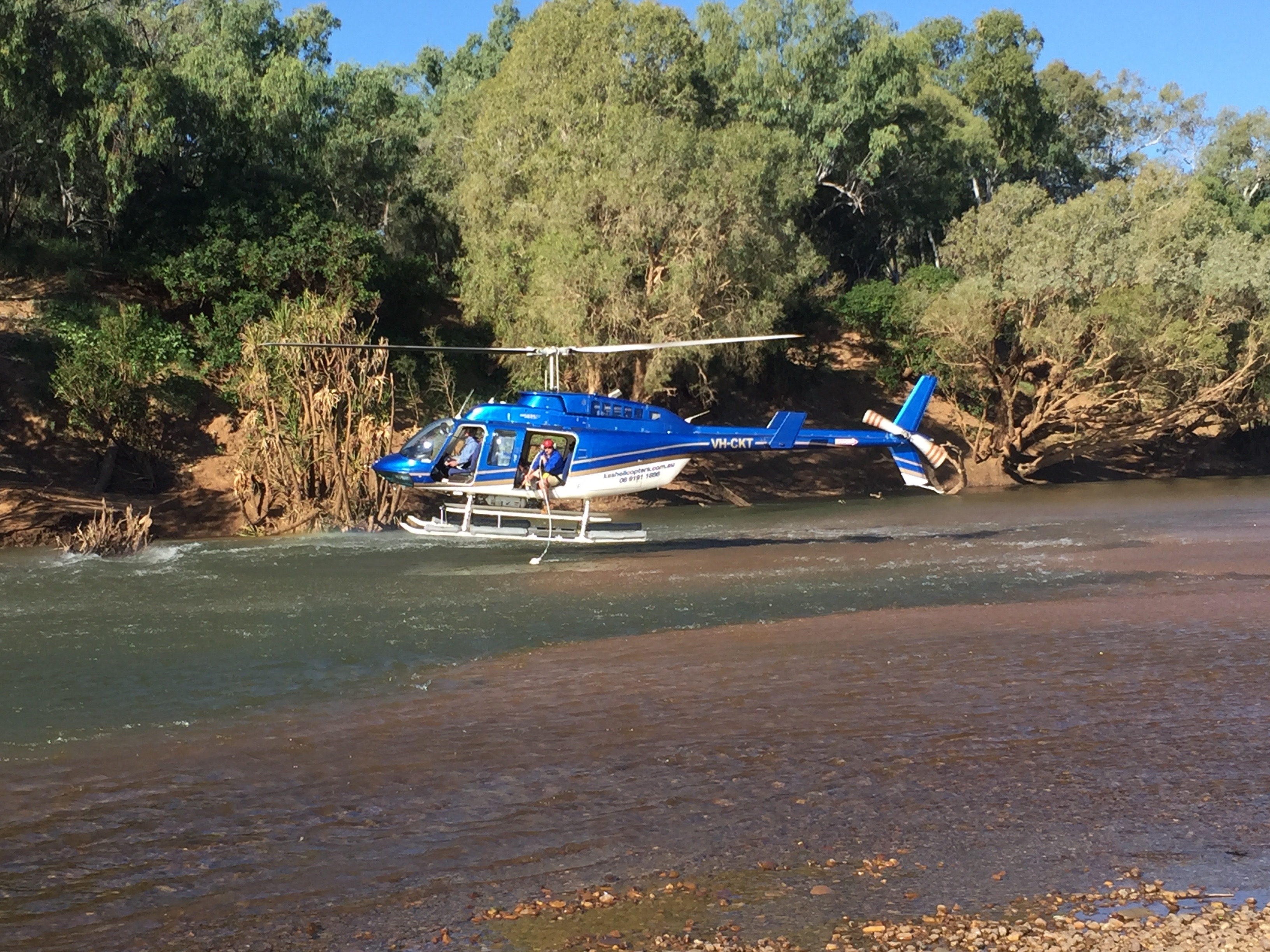 Helicopter hovering over water taking samples from the surface water of the Fitzroy River.
