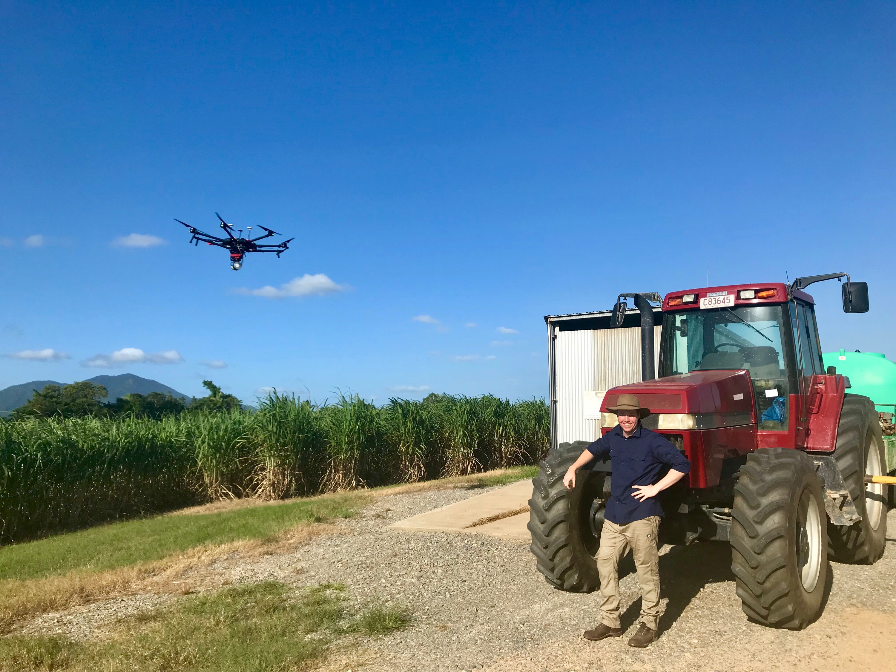 Man stands beside a tractor with a drone in the air