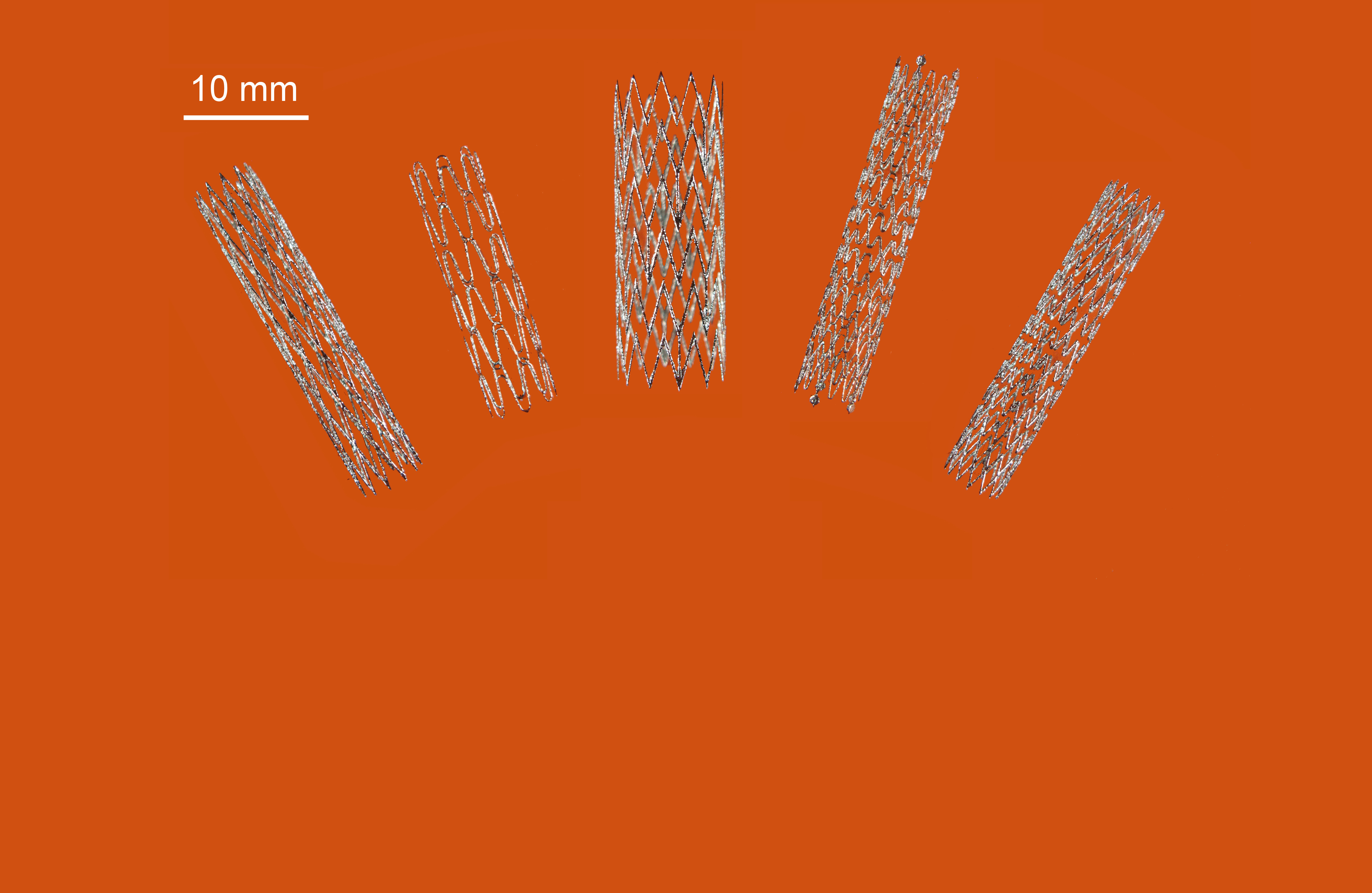 Cloe up view of five 3D prited stents of various sizes on an orange background.