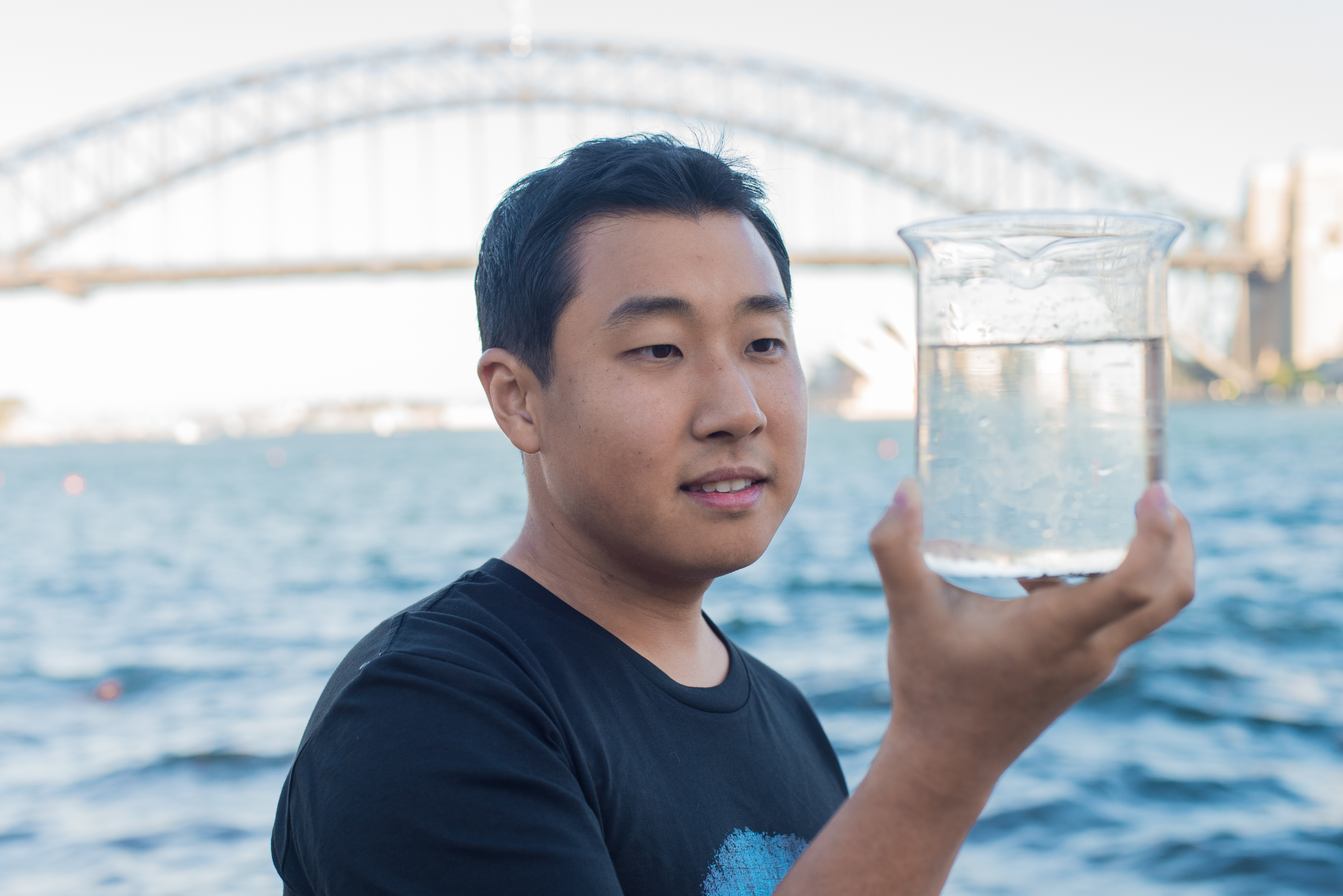 Person holding a beaker of water taken from Sydney Harbour, with the Sydney Harbour Bridge in the backgorund.