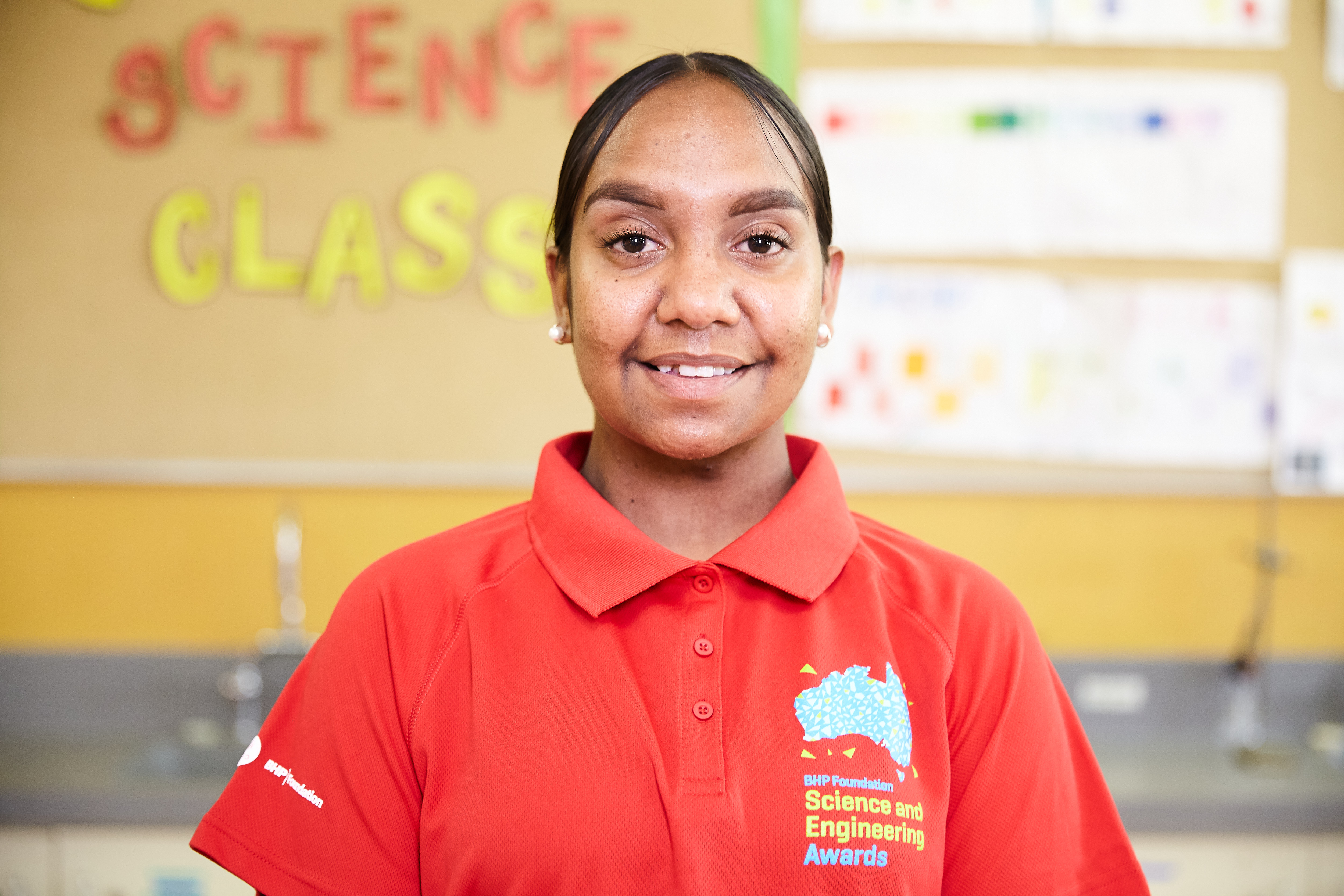Nyheemah Cox wearing a red shirt with the BHP Foundation Science and Engineering Awards logo,and standing in a classroom.