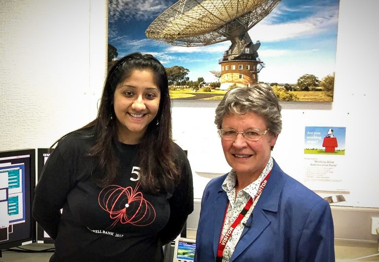 Two women standing together in an office with a picture of a telescope in the background