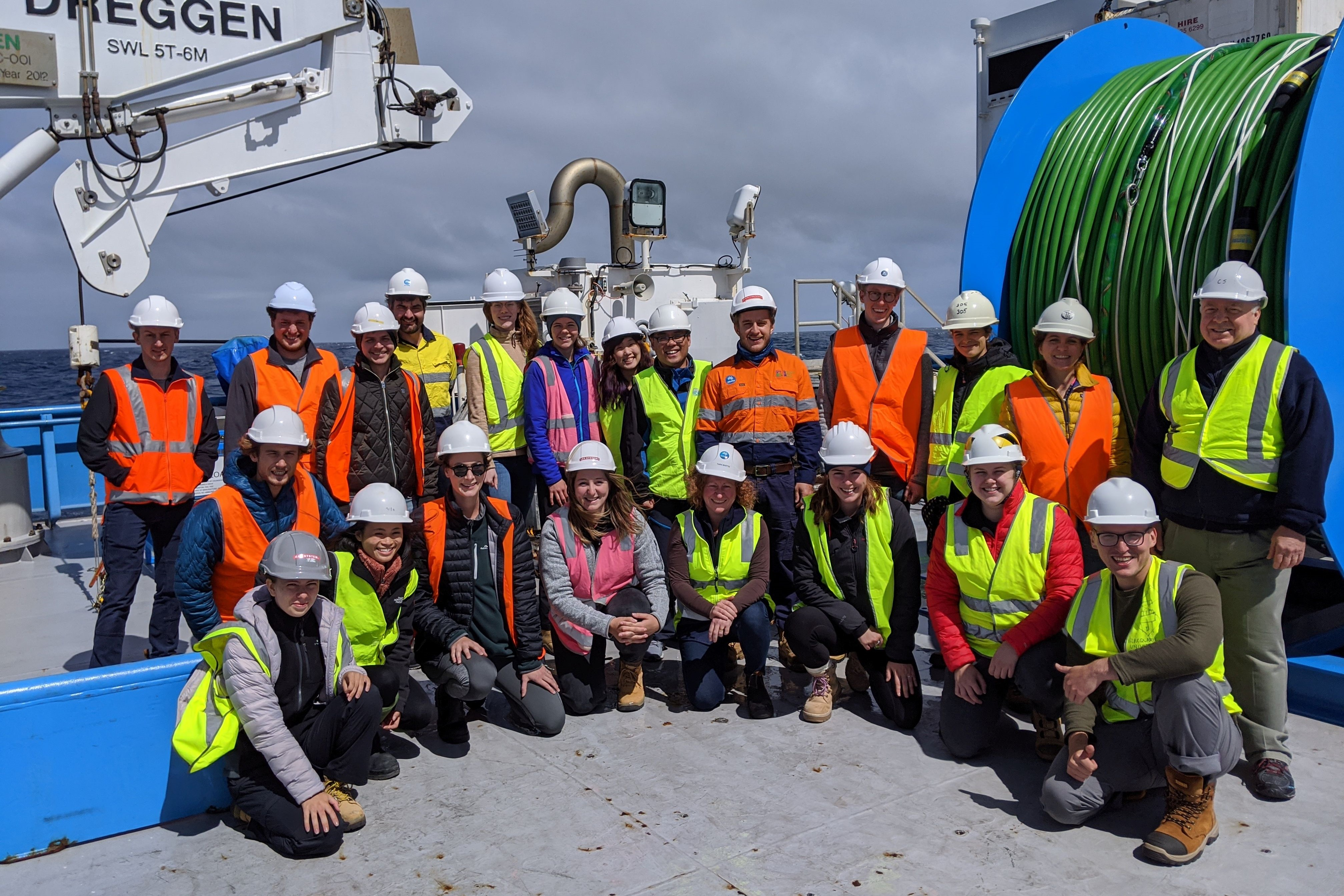 People wearng hi-vis jackets and hard hats gathered for a group photo on board the deck of RV Investigator.