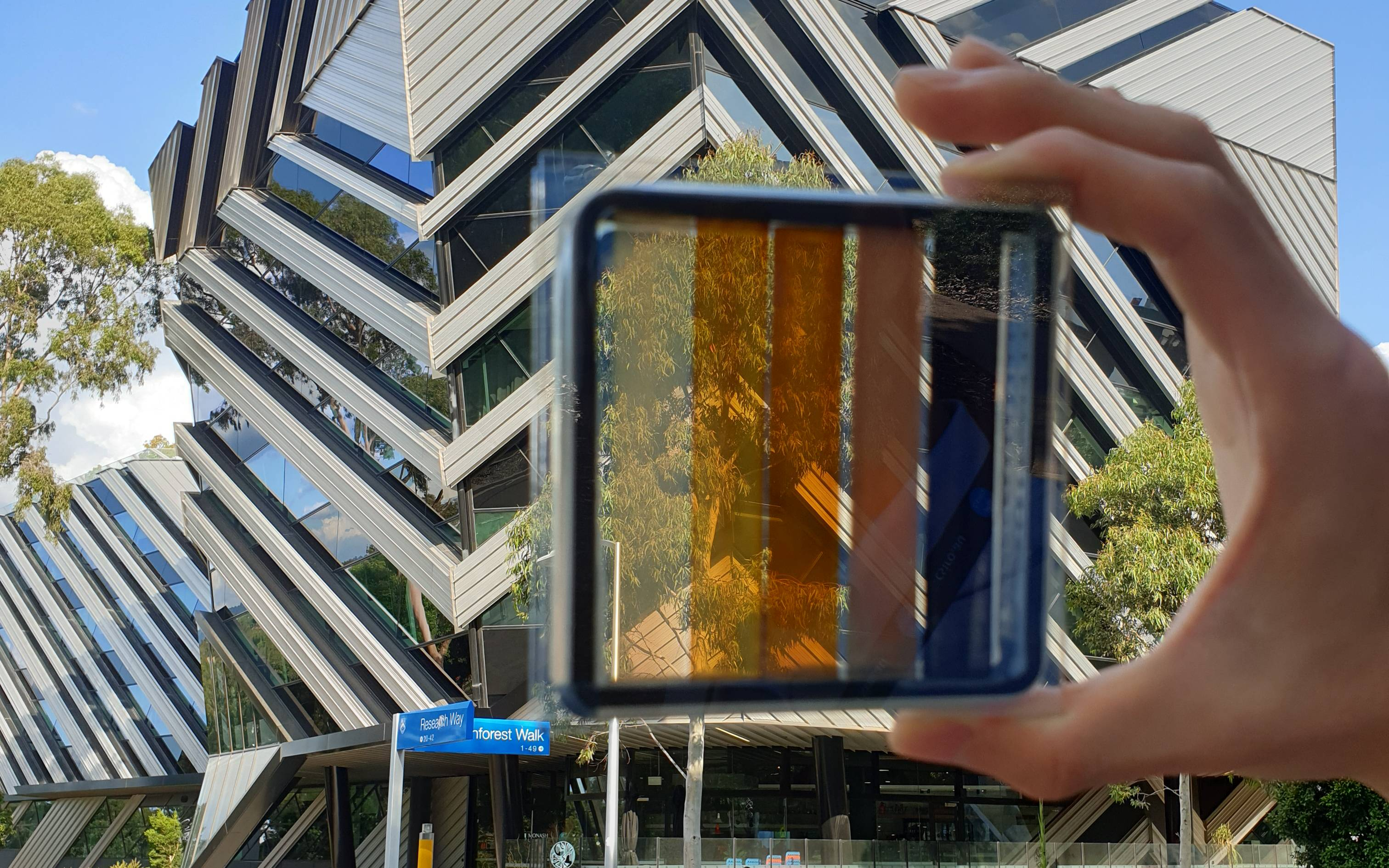A hand holds a solar cell in front of a building.