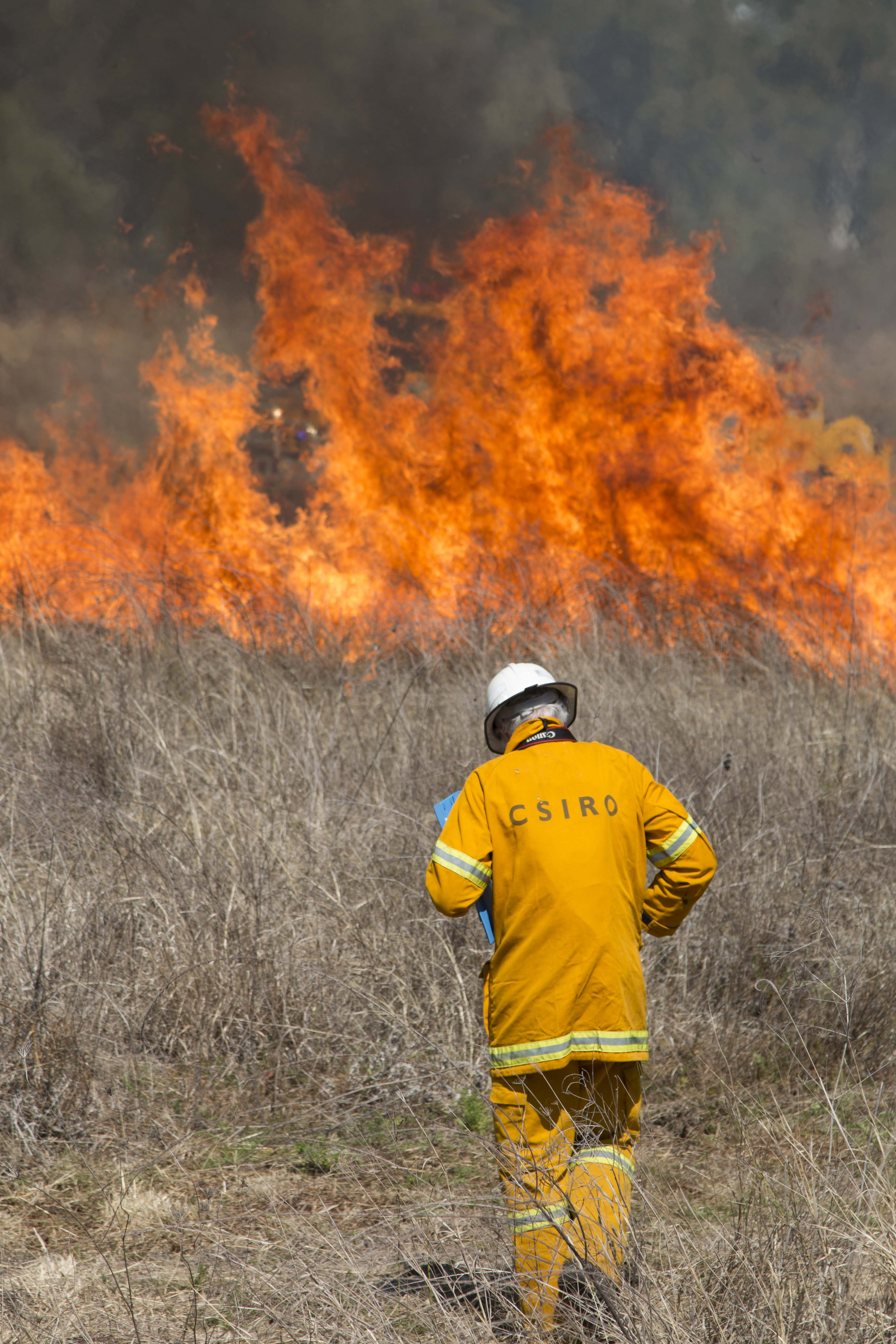 Man standing in front of grass fire.