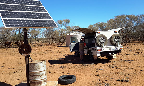 Person standing next to a 4WD vehicle parked near a solar powered monitoring station in bushland.