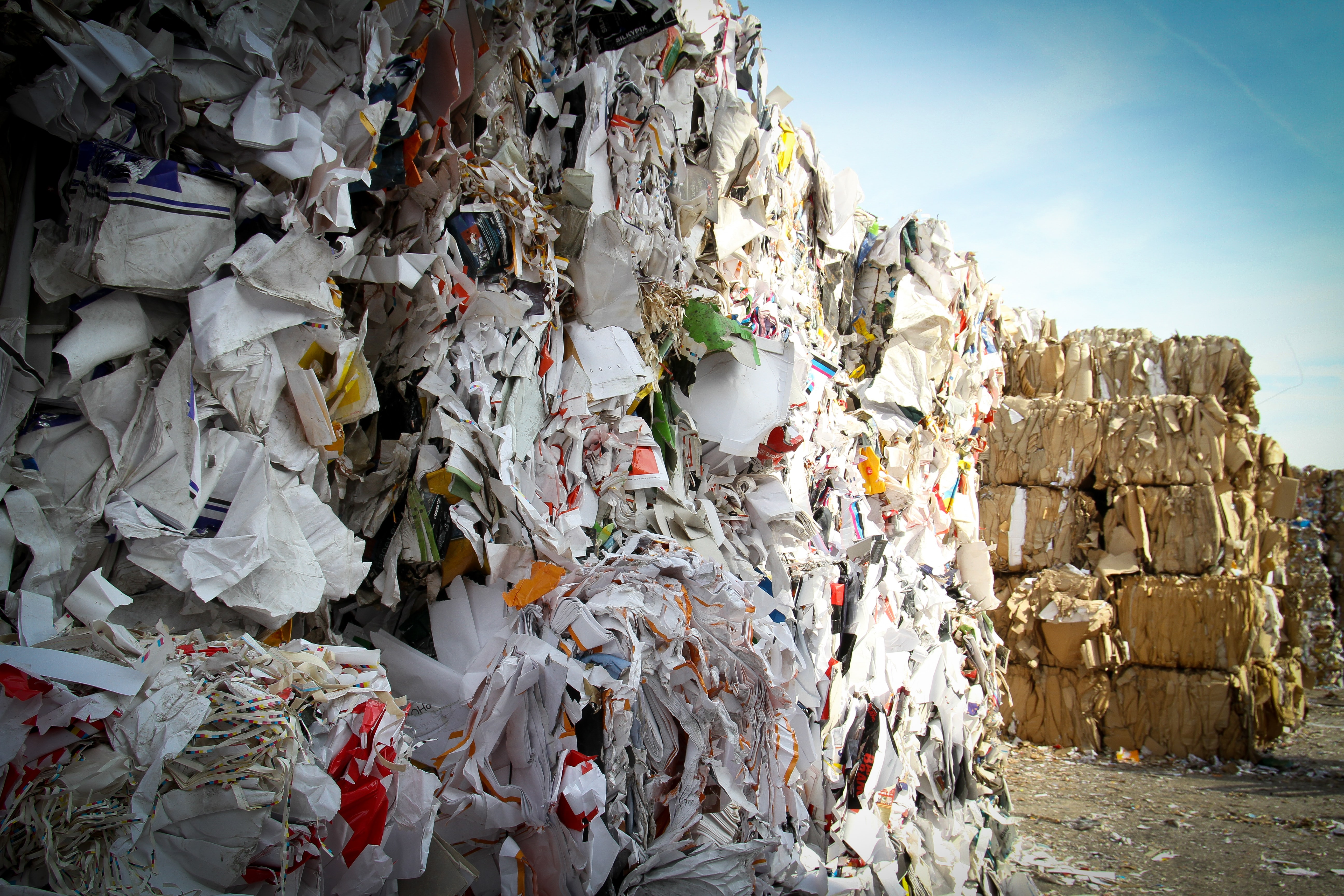Large stacks of compress paper waste ready for recycling.