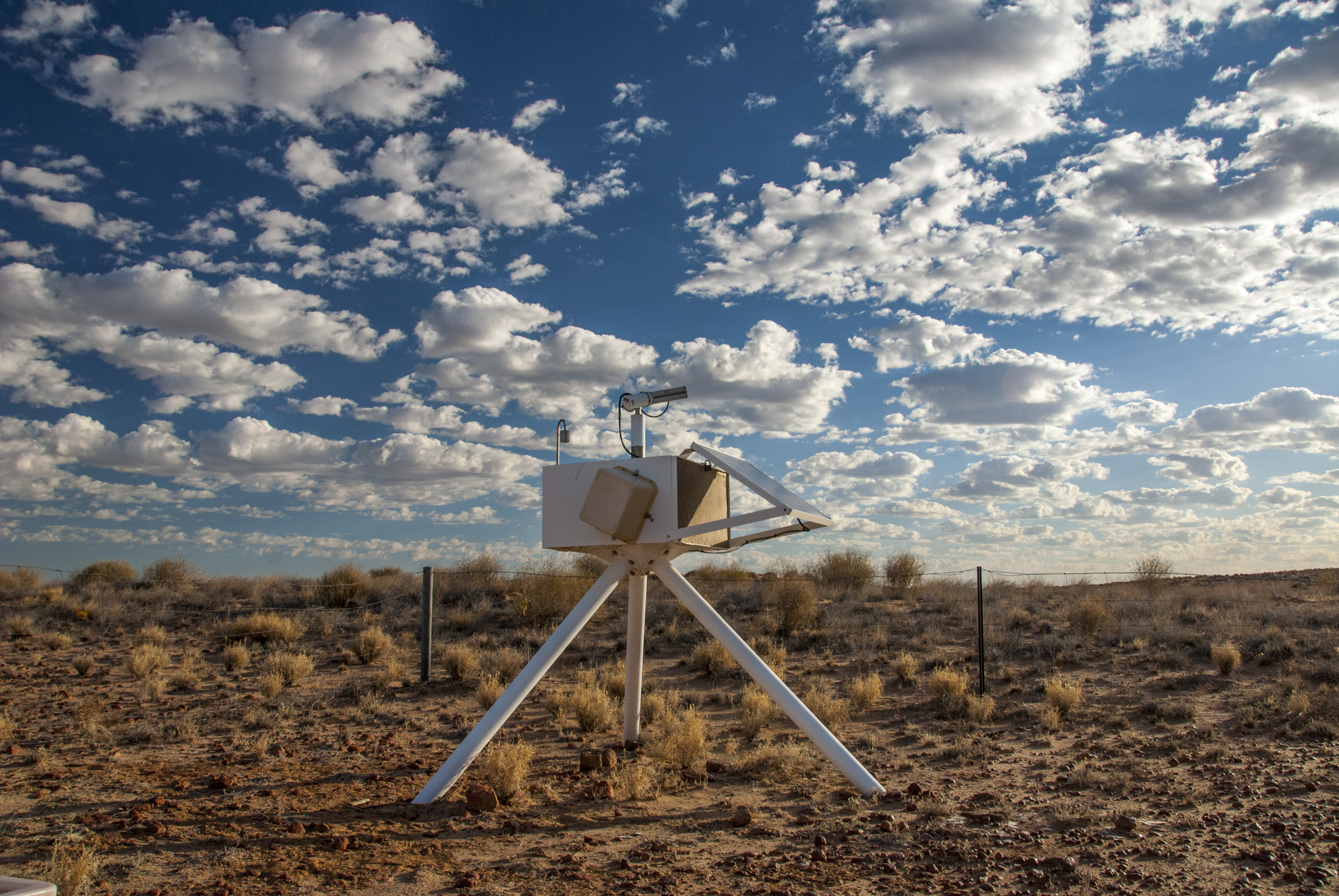An aerospan instrument on scrubby plain beneath cumulus clouds