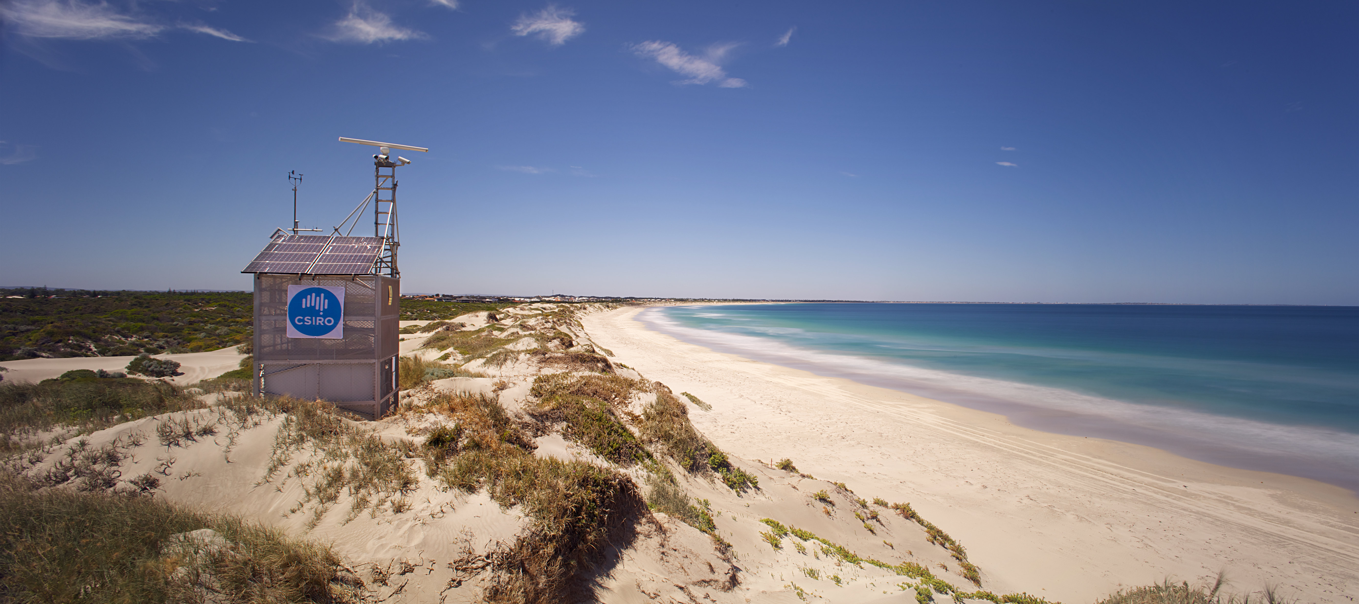 A small hut on a dune behind a beach bearing the CSIRO logo