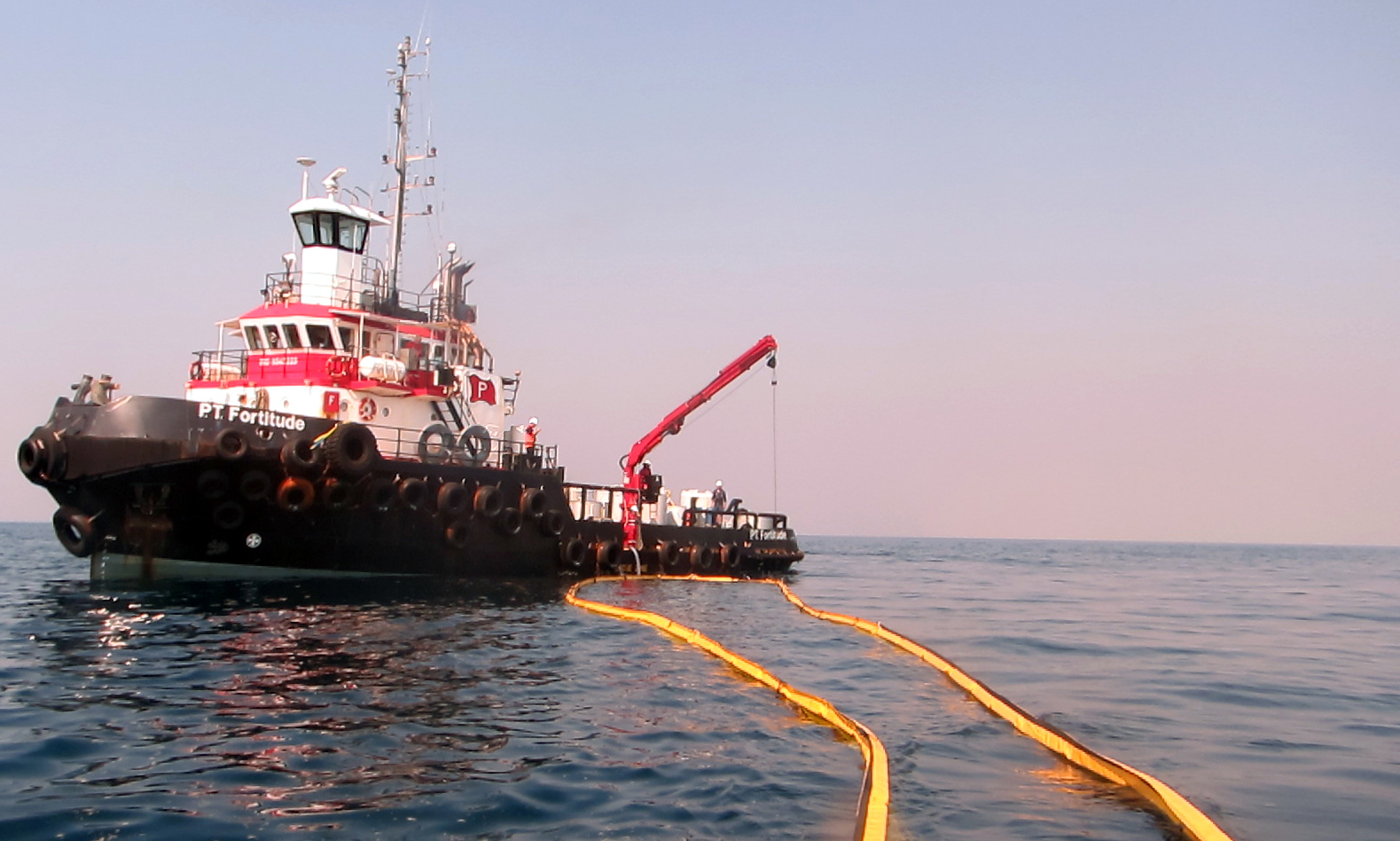 A tug boat is picture with boom lowered into the water