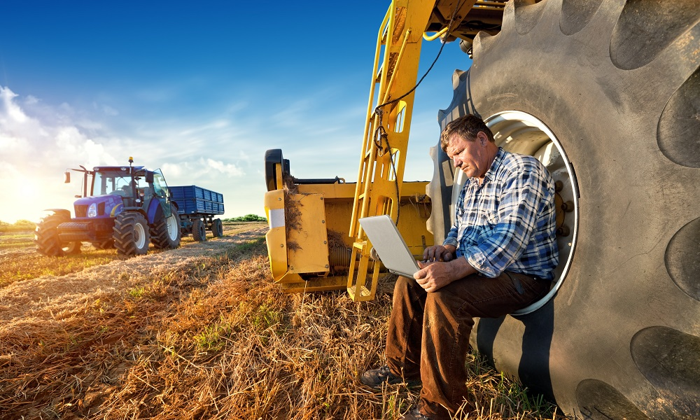 A man sits on a large tractor tire with a computer on his lap. A harvester is seen in the background.