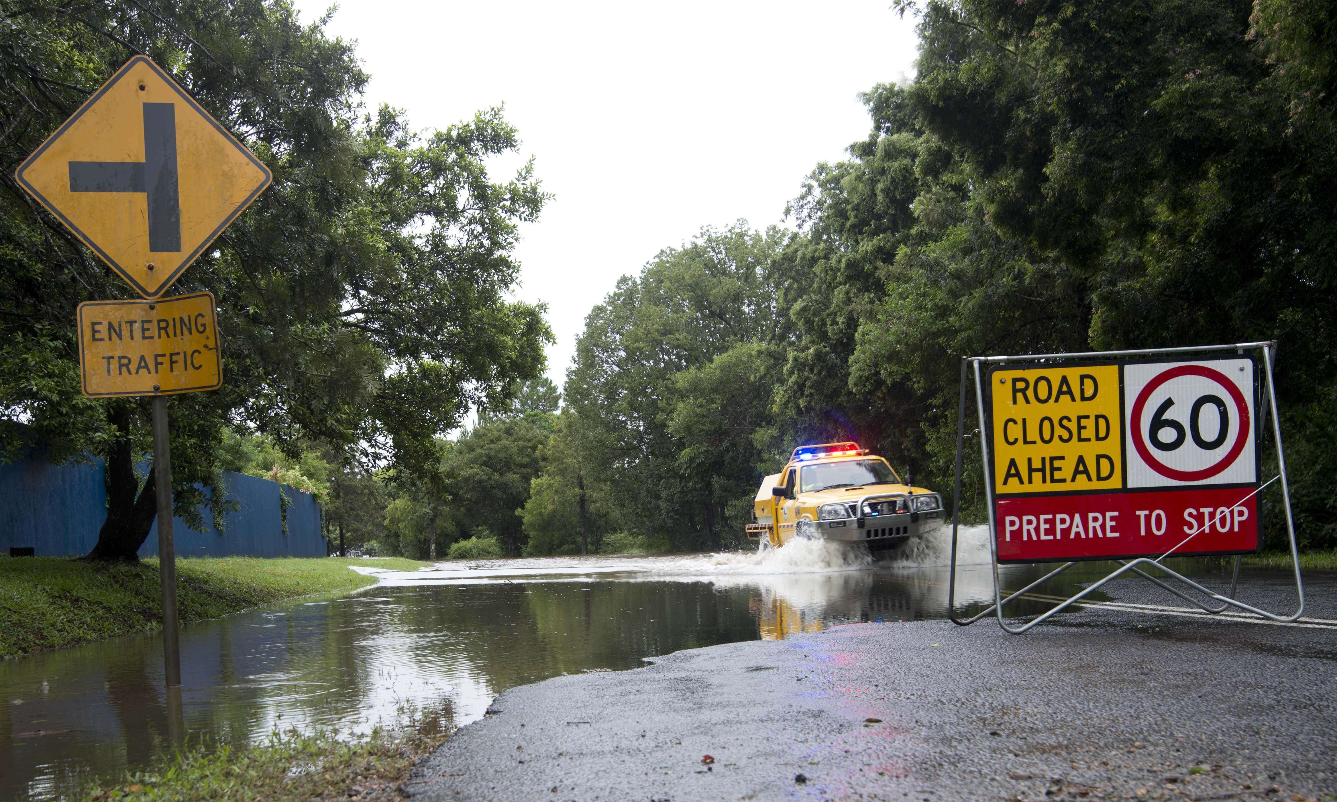 A car passes through a flooded road. A road sign saying 'road closed ahead' is visible in the foreground
