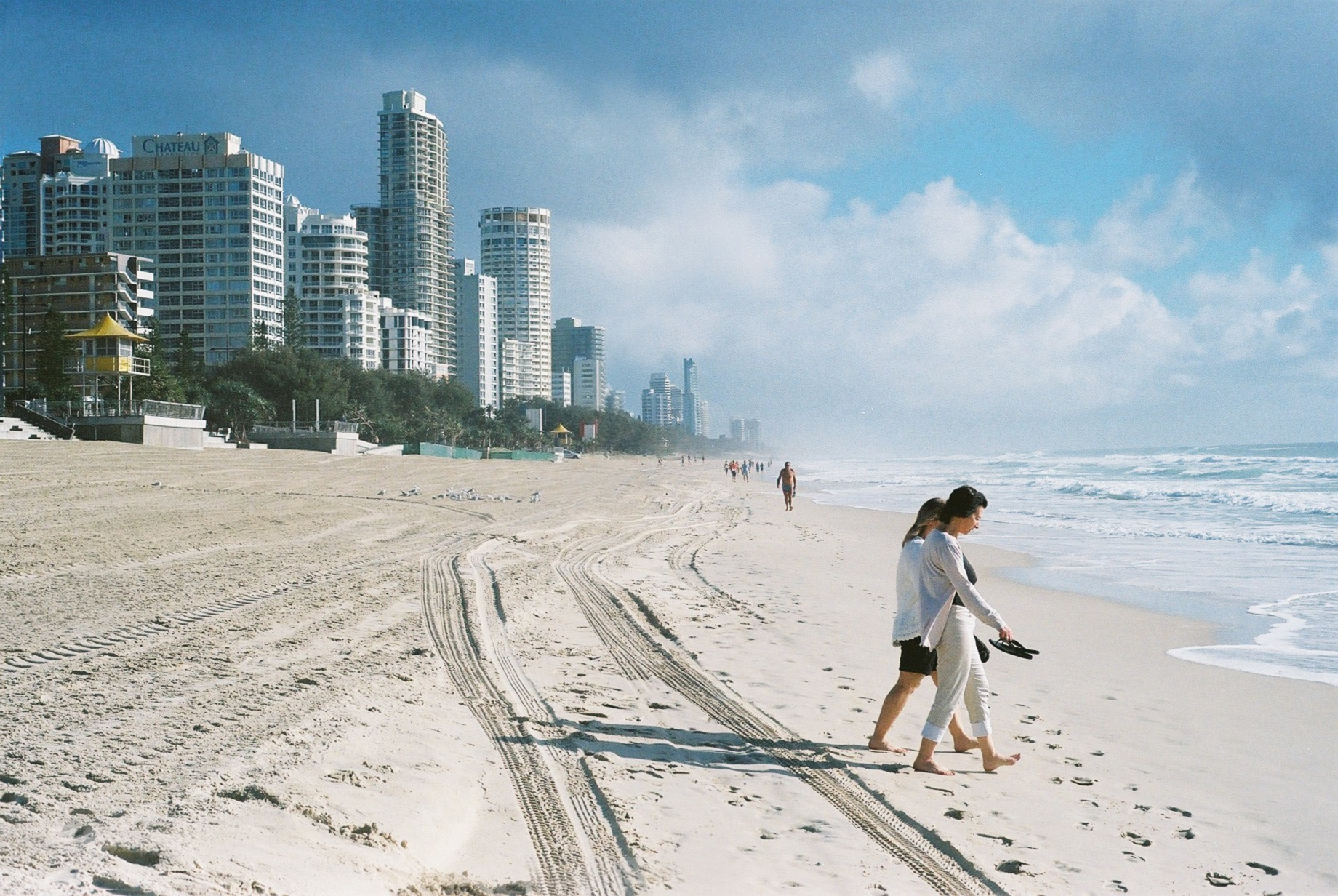 Two ladies walk towards the water on Gold Coast beach. High rise in the background.