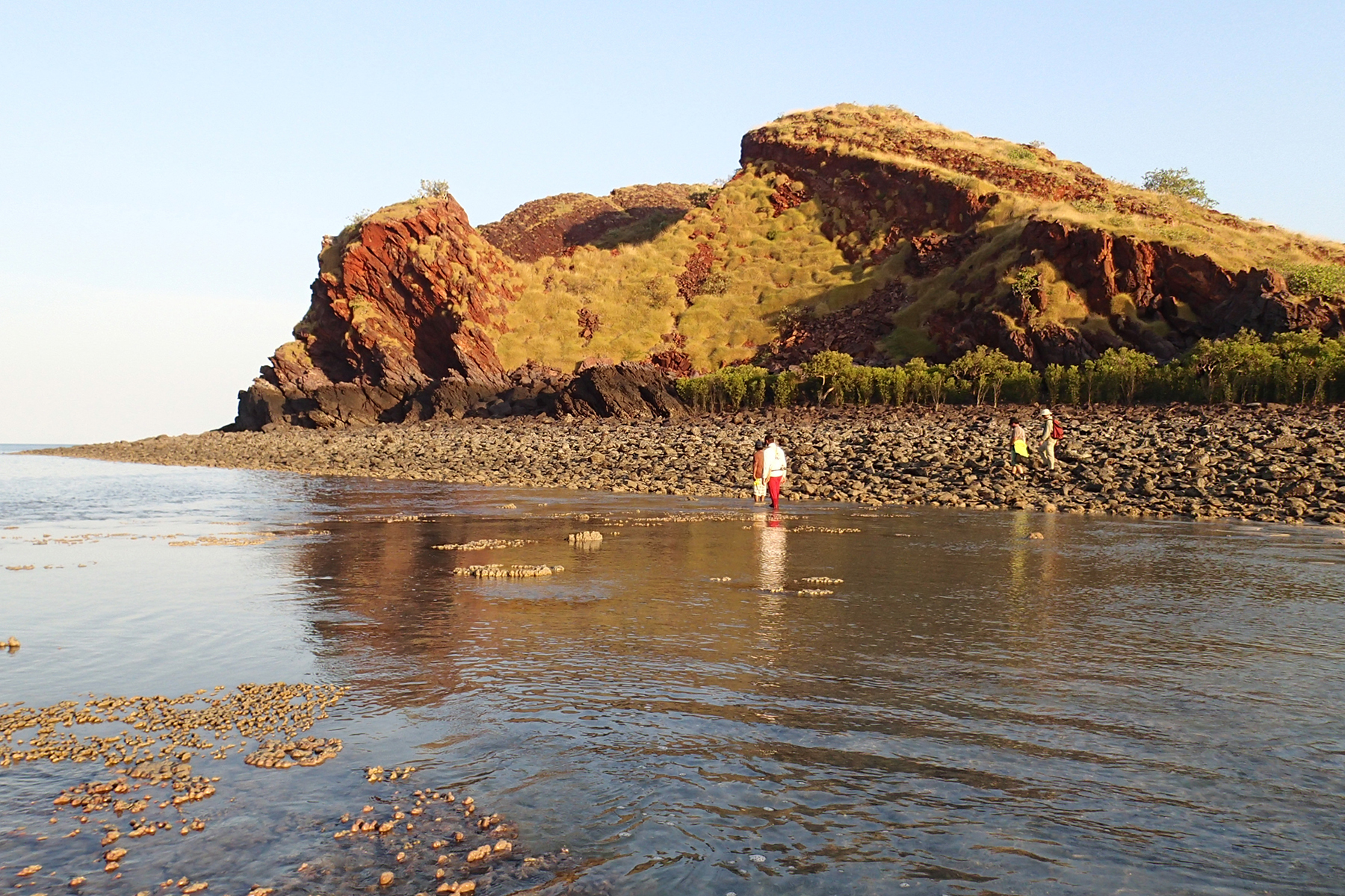 People wade through shallow water infront of a rocky mound
