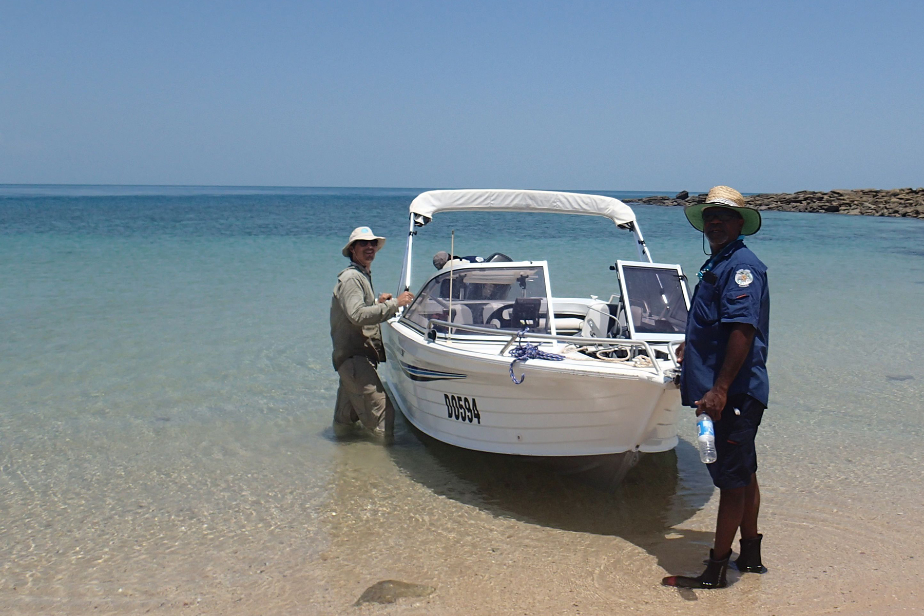 CSIRO scientist stands with an indigenous ranger infront of boat on the shore