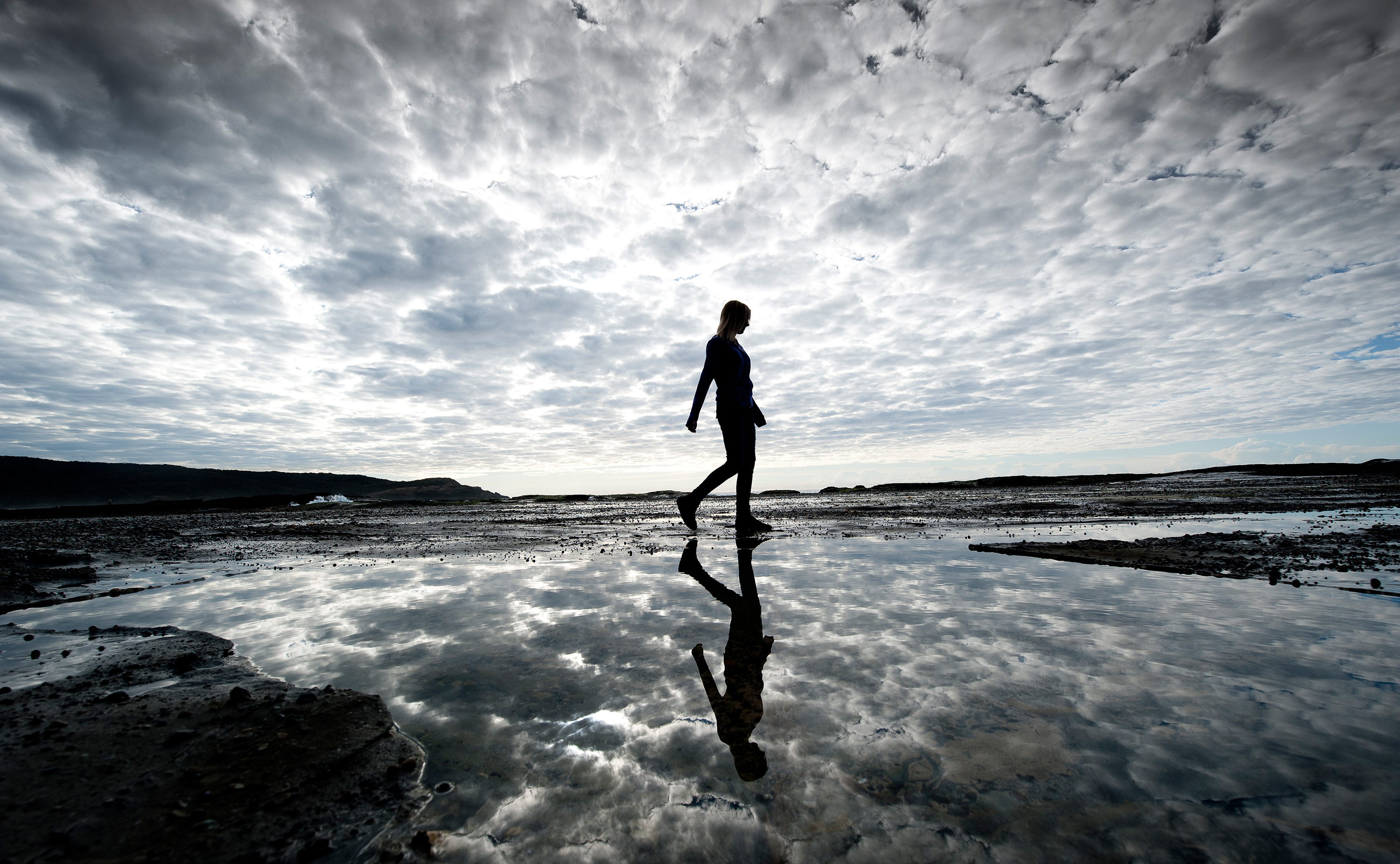 A person walks along a rock platform with sea and cloudy sky