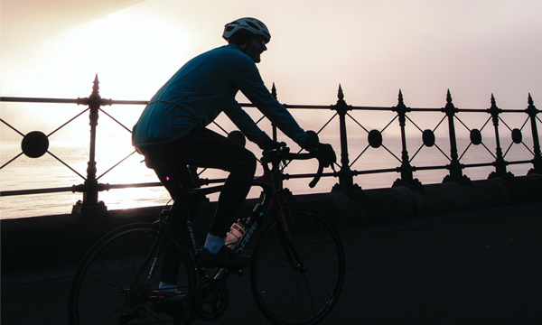 Cyclist under Sydney harbour bridge surrounded by fog