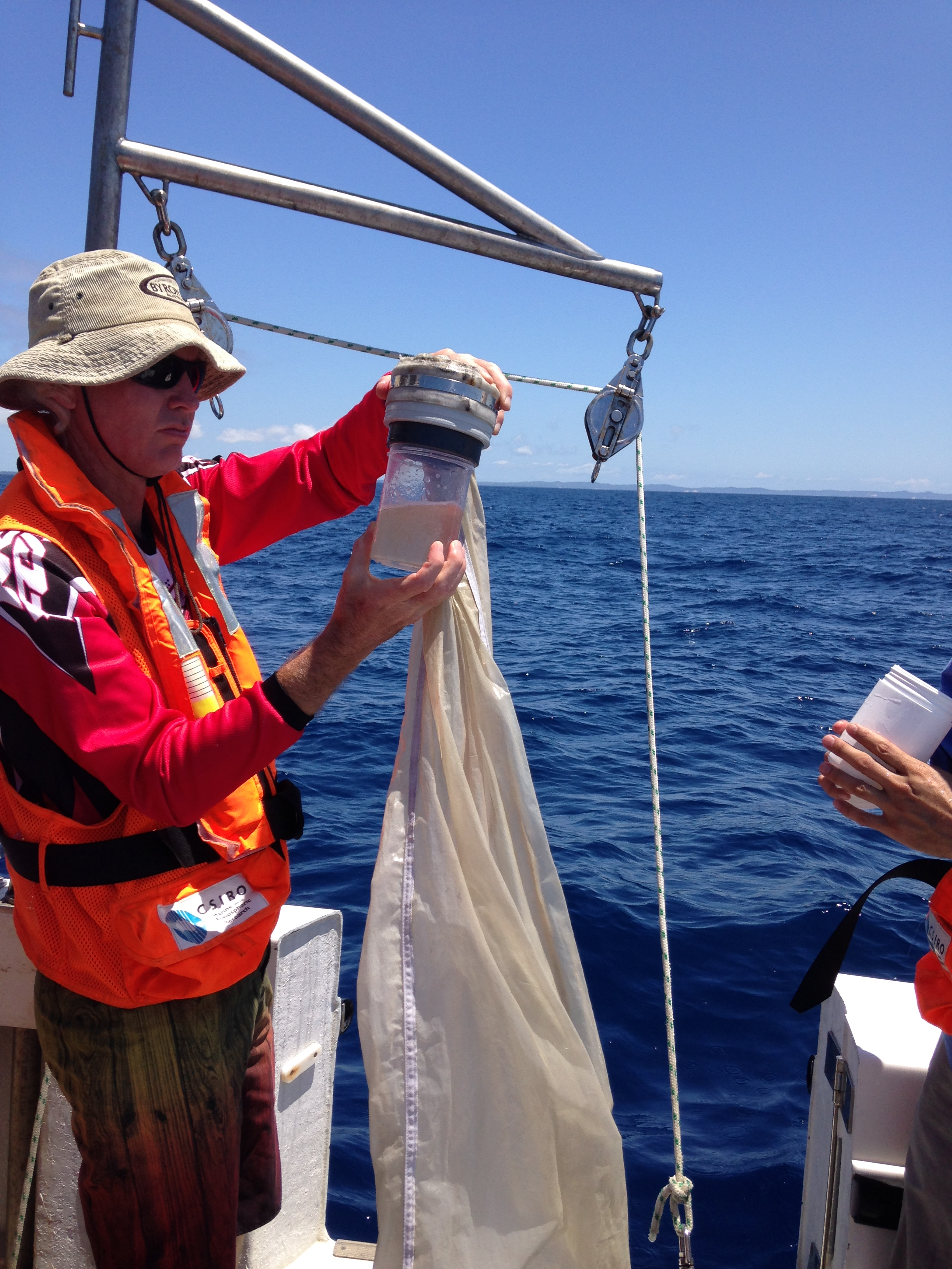 Man holds a zooplankton sample, seen standing on a boat with ocean in the distance.